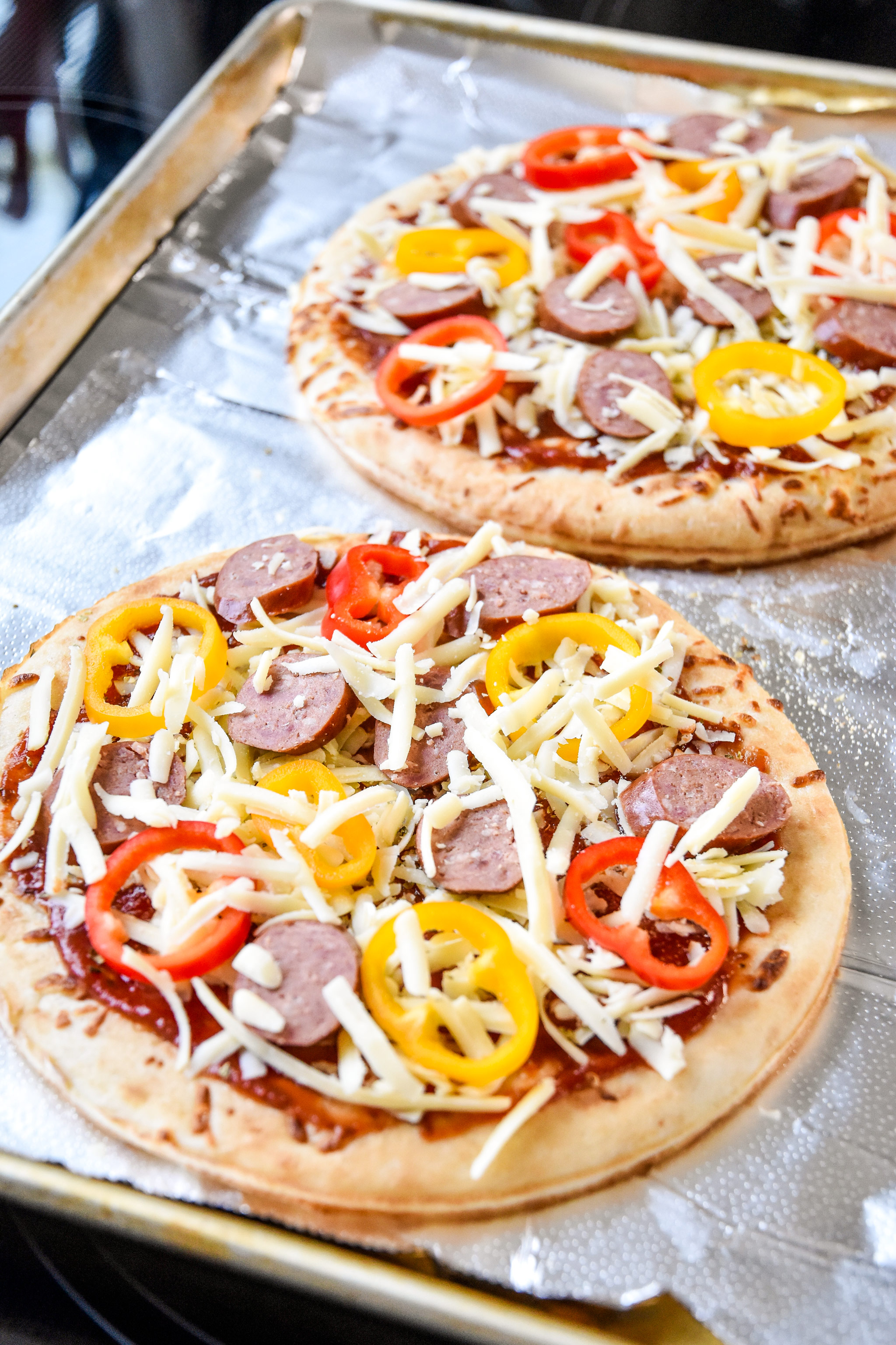 sausage and pepper personal pizzas just assembled and about to go in the oven