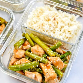 meal prep spicy chicken asparagus meal with rice in a glass meal prep container