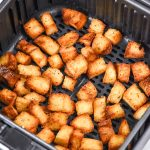 homemade croutons in an air fryer basket.
