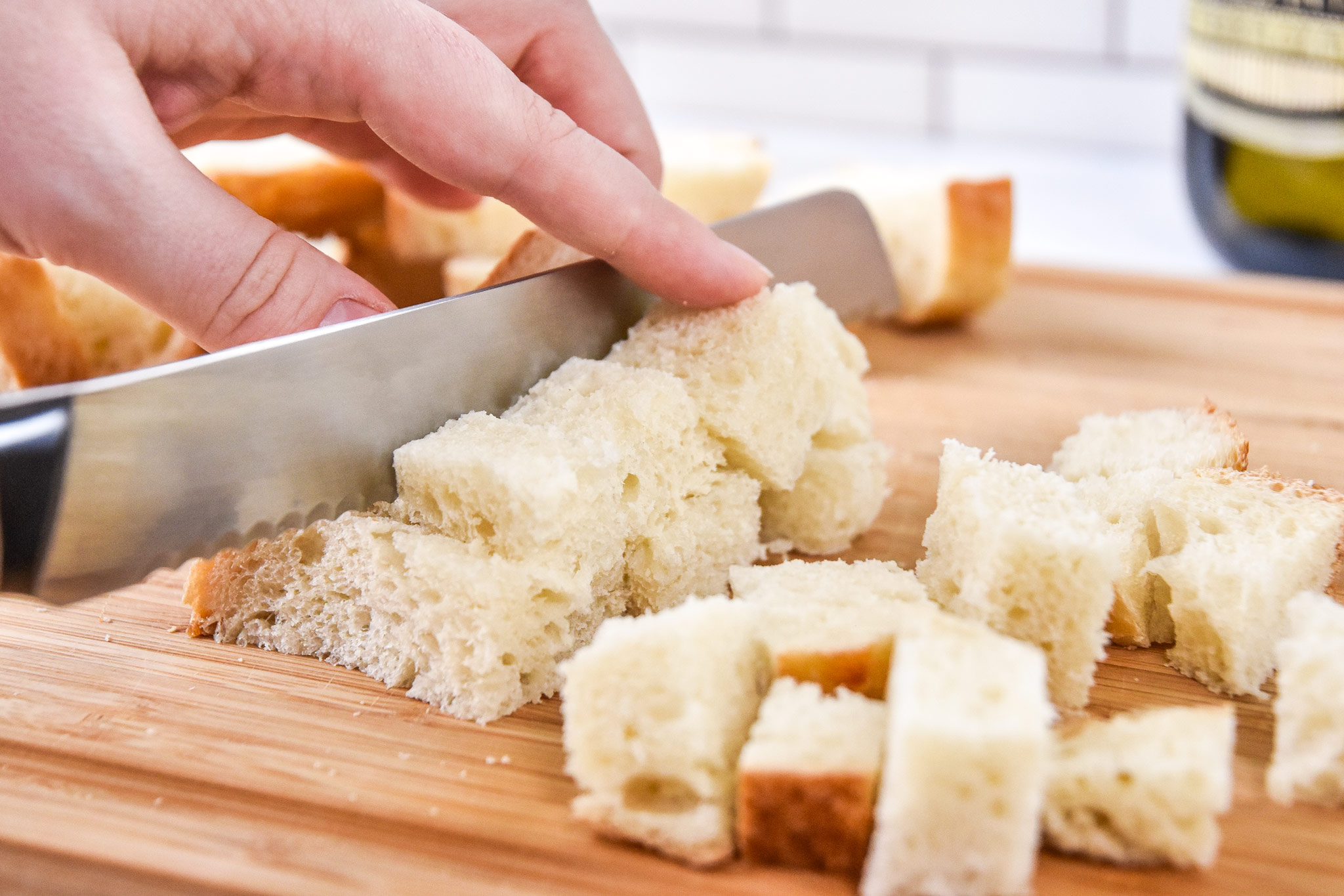 cutting sourdough bread into cubes for cruotons.