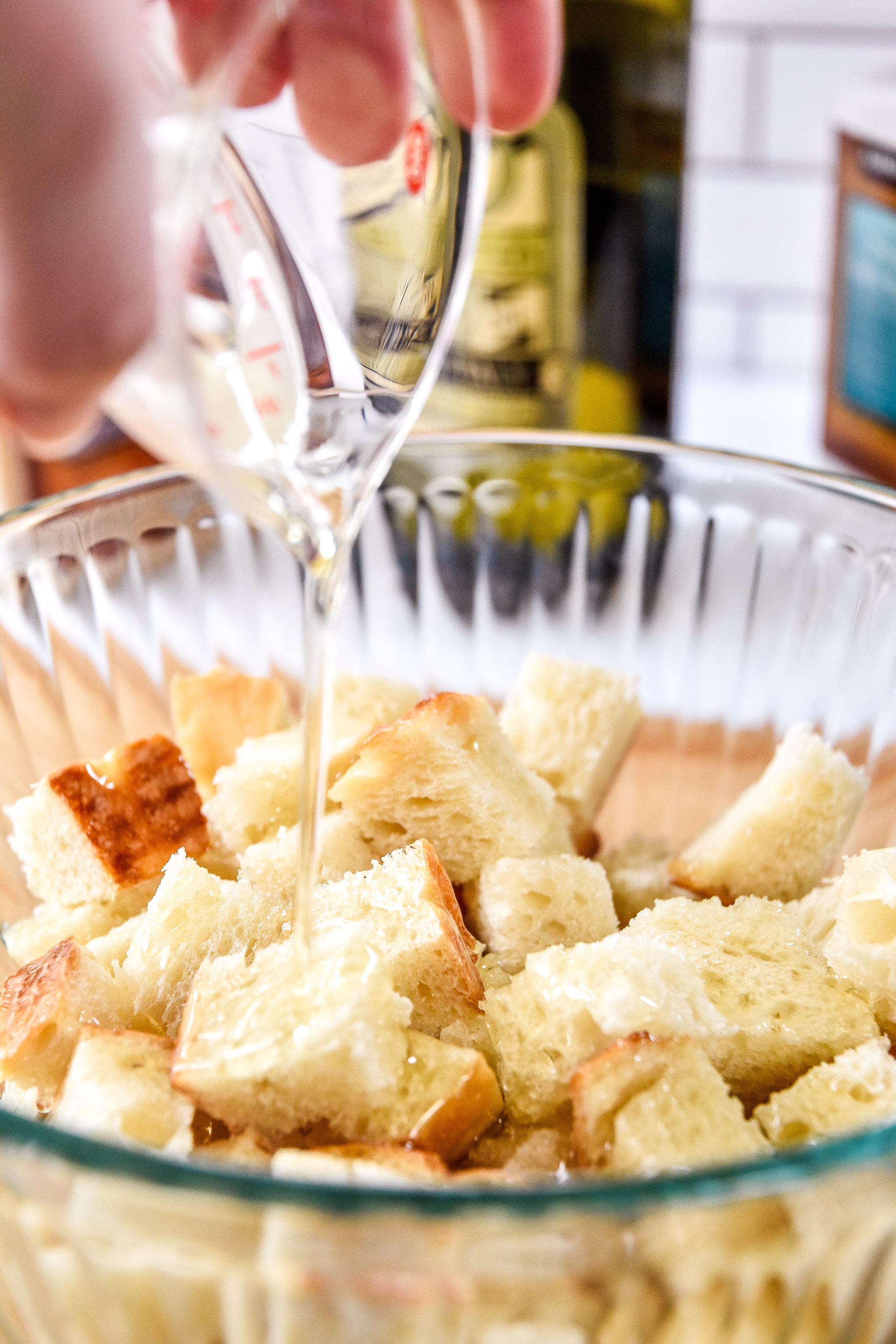 pouring oil on bread cubes to make croutons