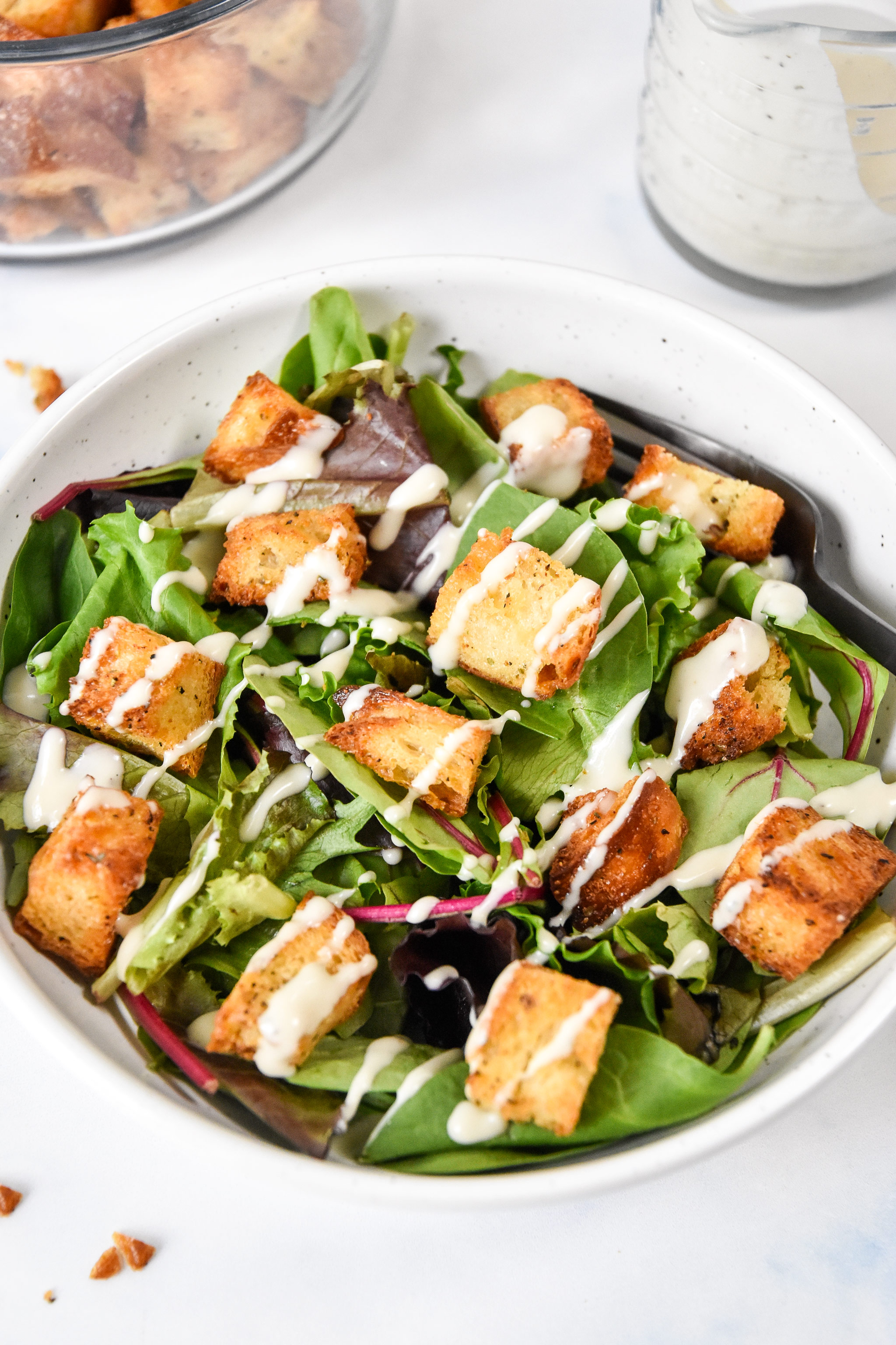 homemade croutons in a salad with ranch drizzle.