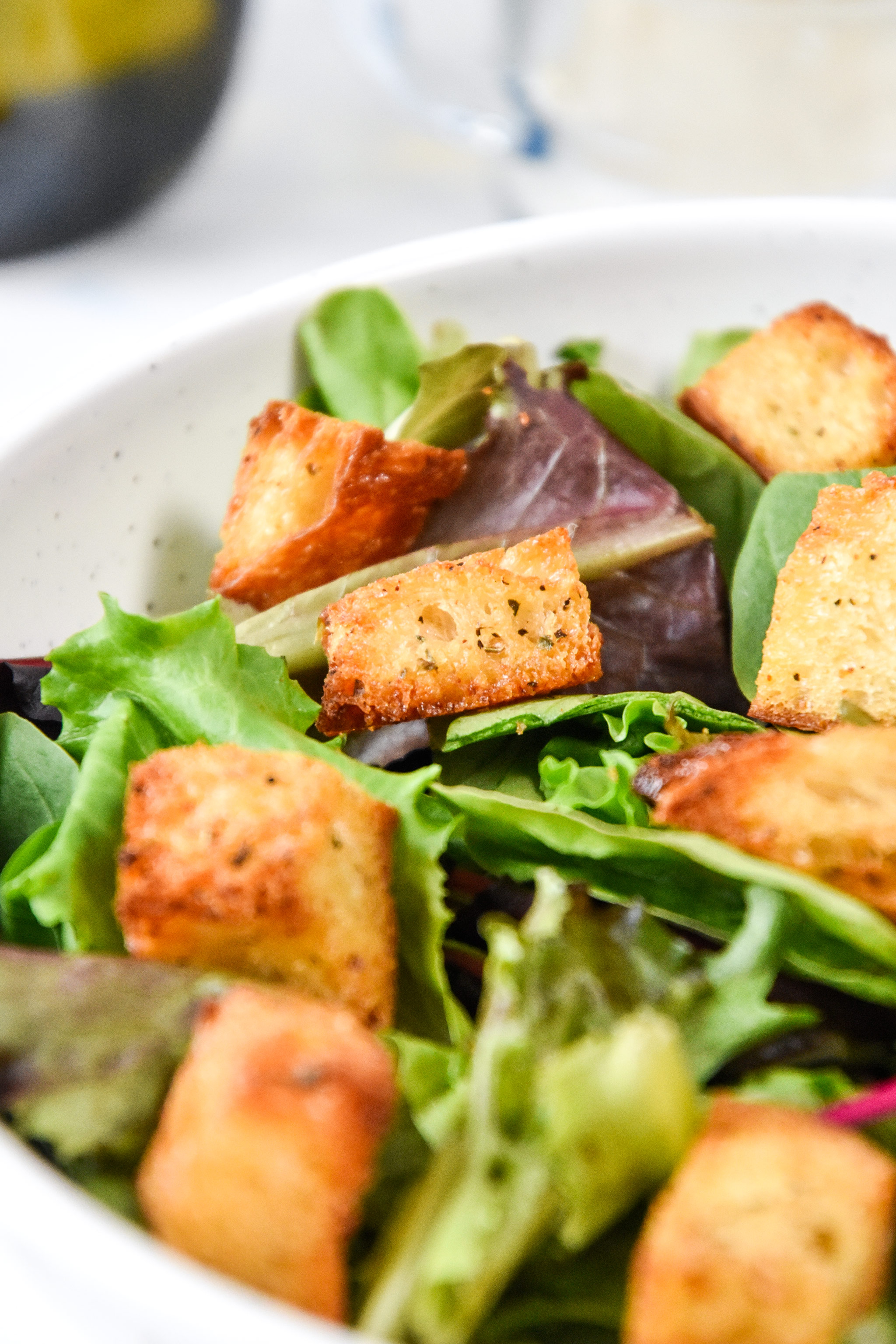 homemade croutons on a green salad in a bowl.