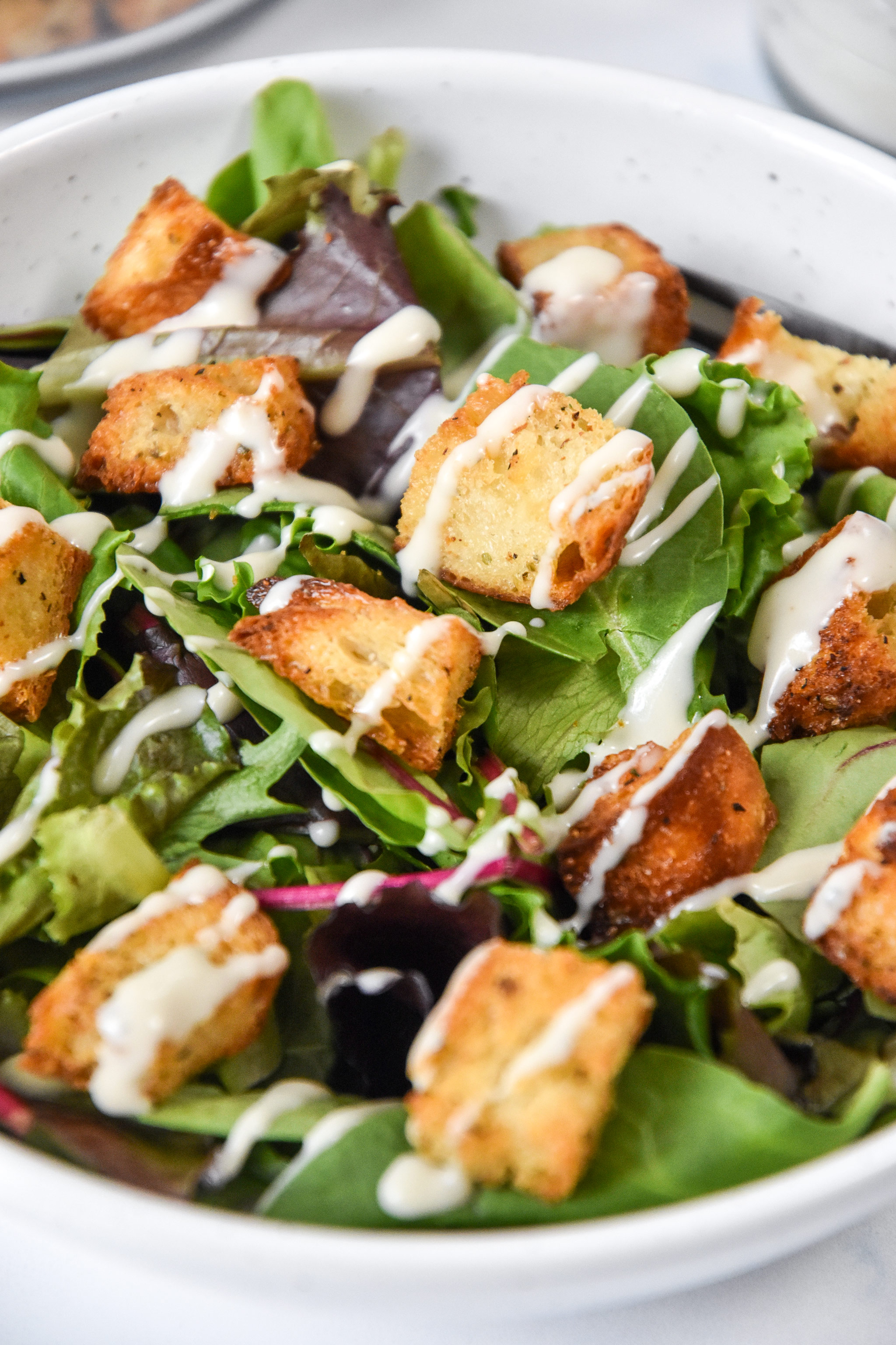 homemade croutons on top of a green salad with ranch drizzle.