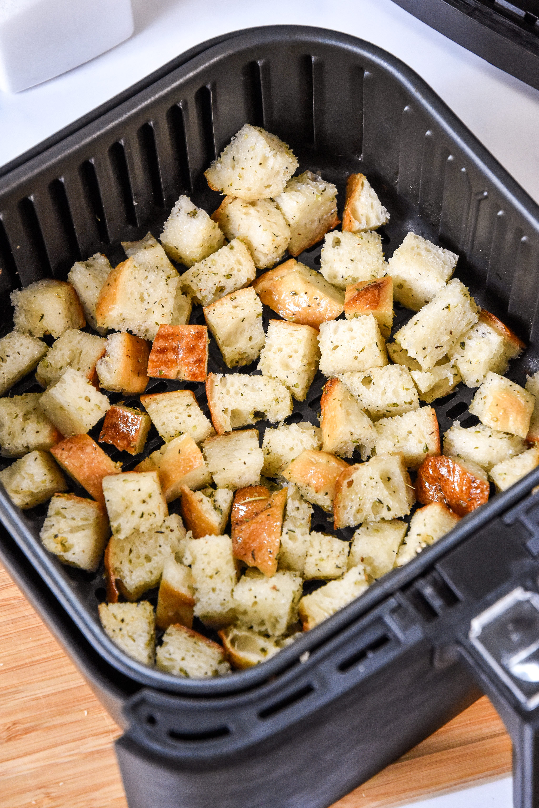 bread cubes in an air fryer basket before cooking.