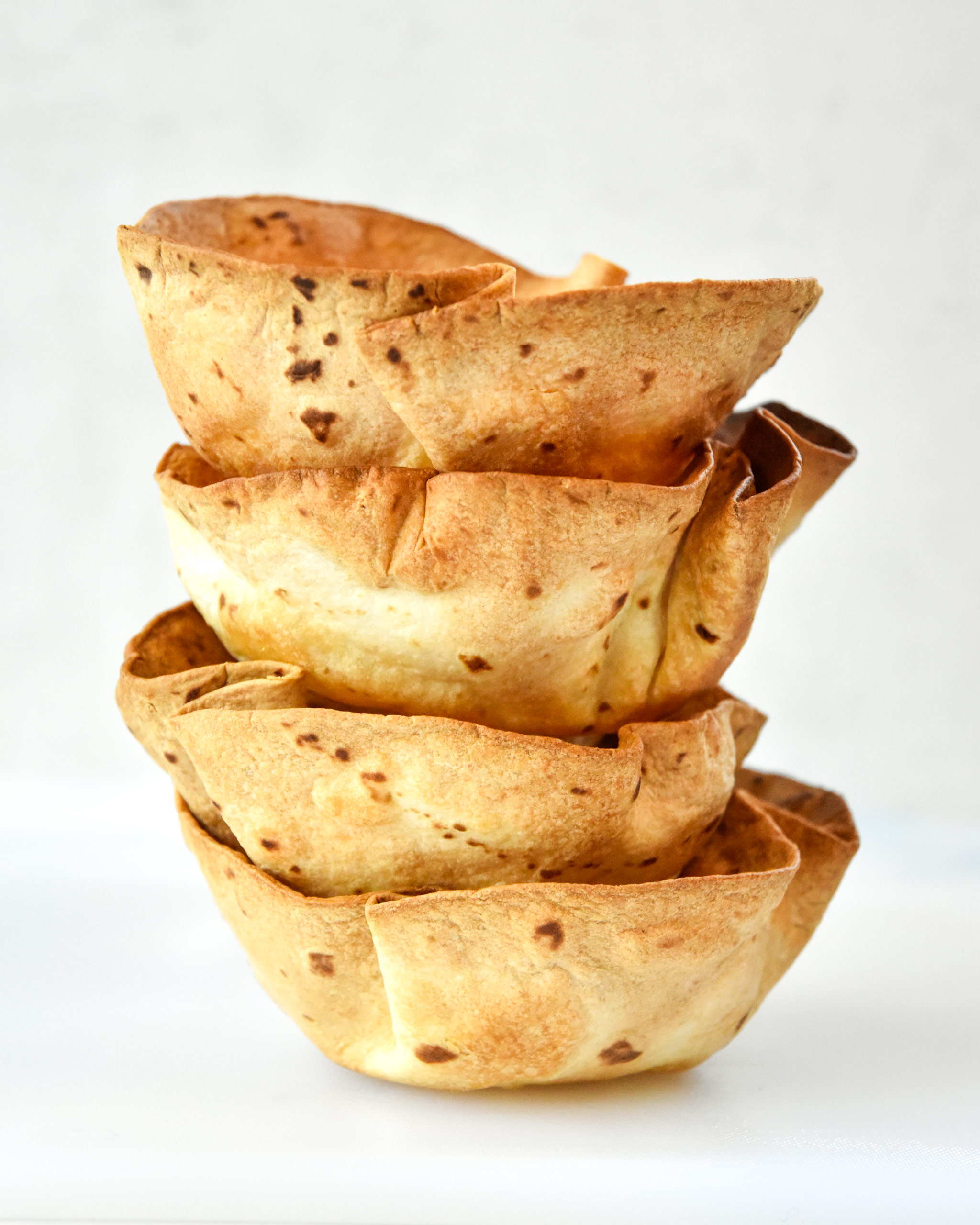 4 flour tortilla bowls stacked with a white background
