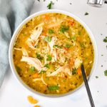 instant pot ginger chicken & rice soup in a bowl with a spoon