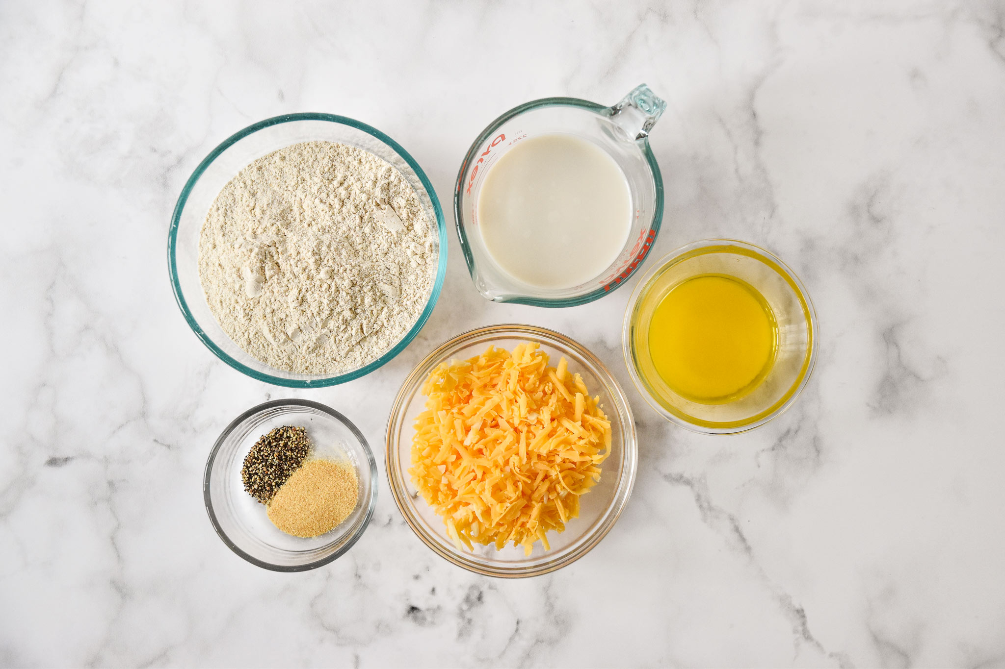 ingredients in separate bowls for the pancake mix cheddar drop biscuits.