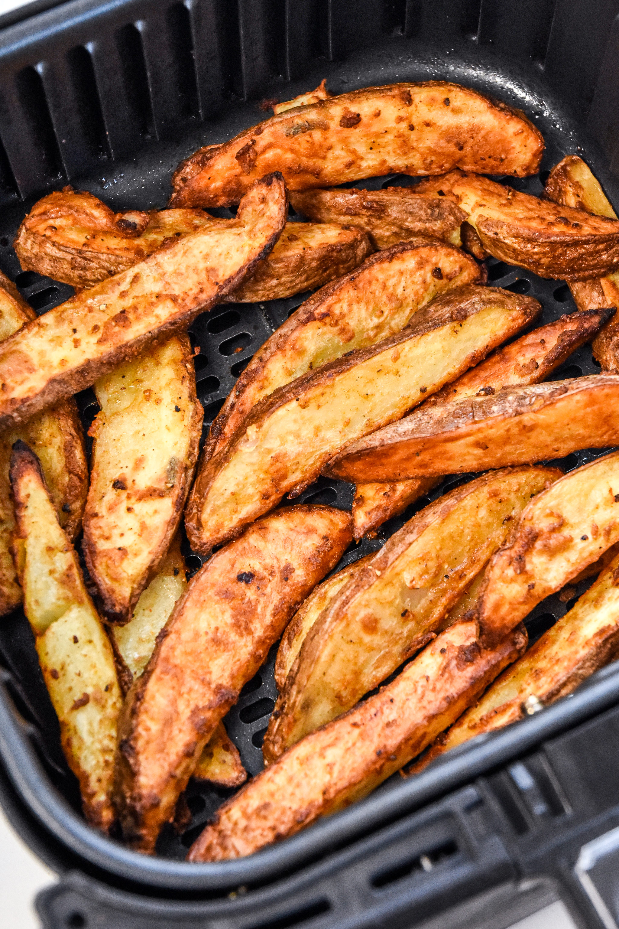 close up of cooked jojo potato wedges in an air fryer basket.