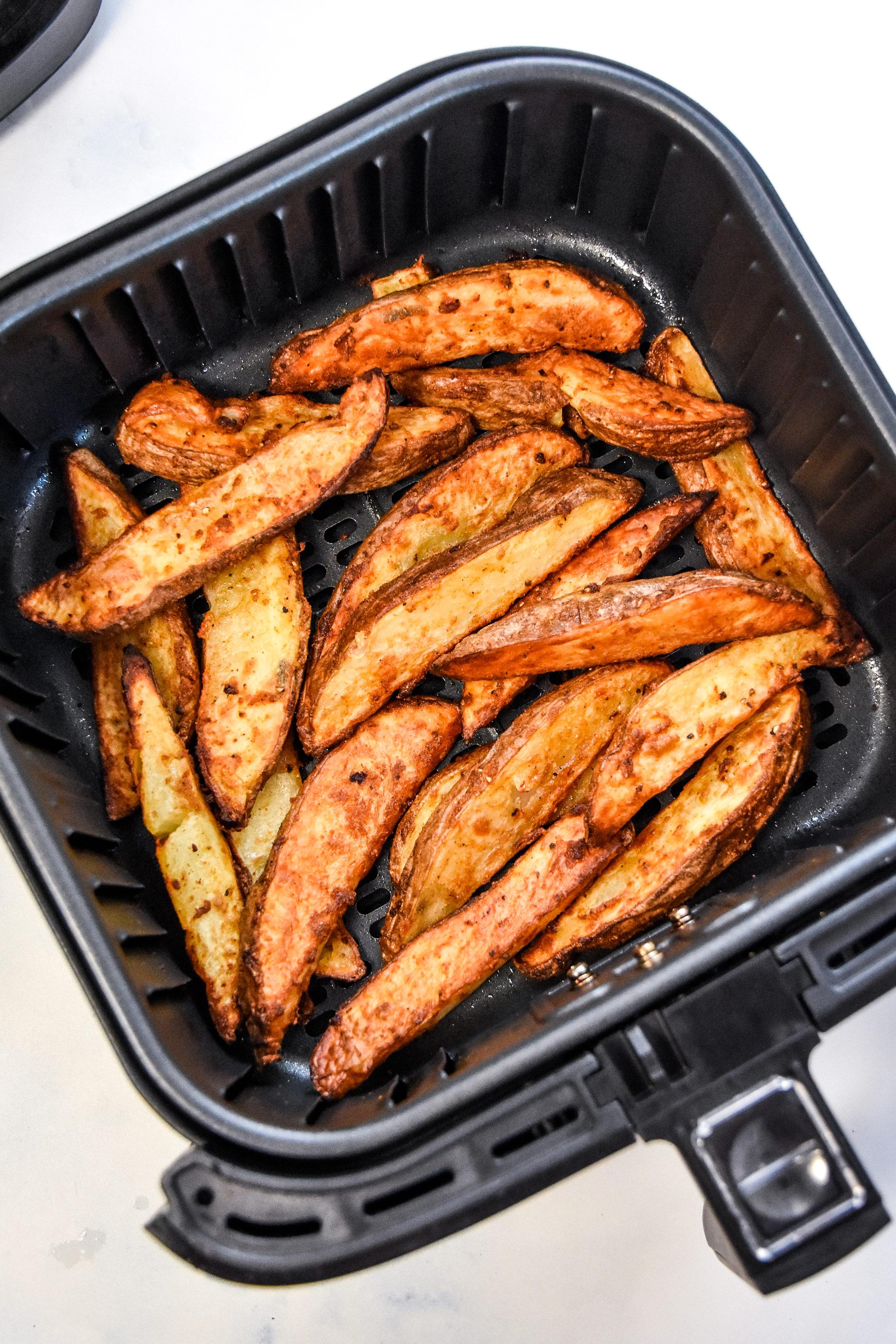 air fryer jojo potato wedges cooked in the air fryer basket.