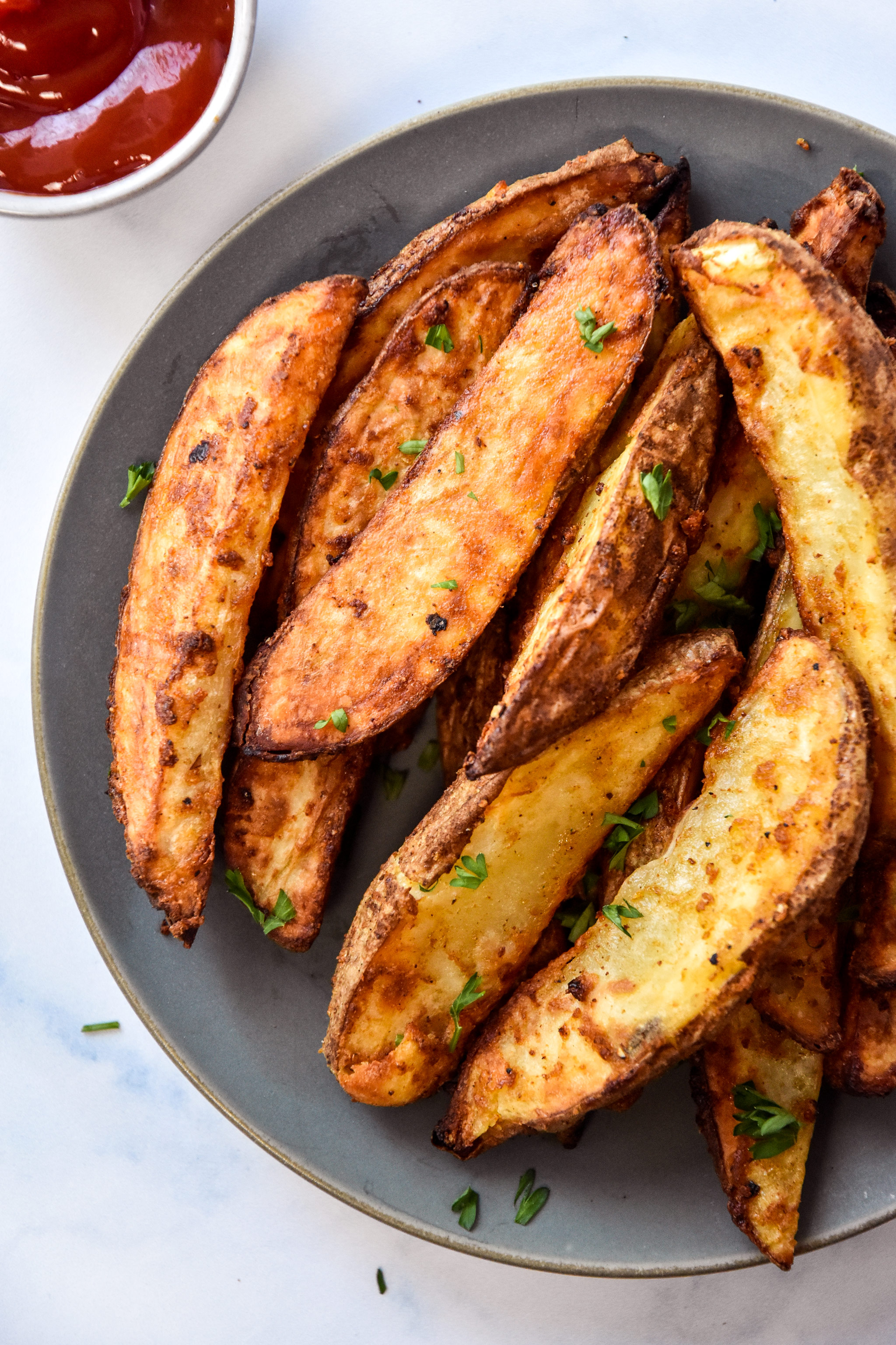 air fryer jojo potato wedges on a plate with parsley sprinkled on top.