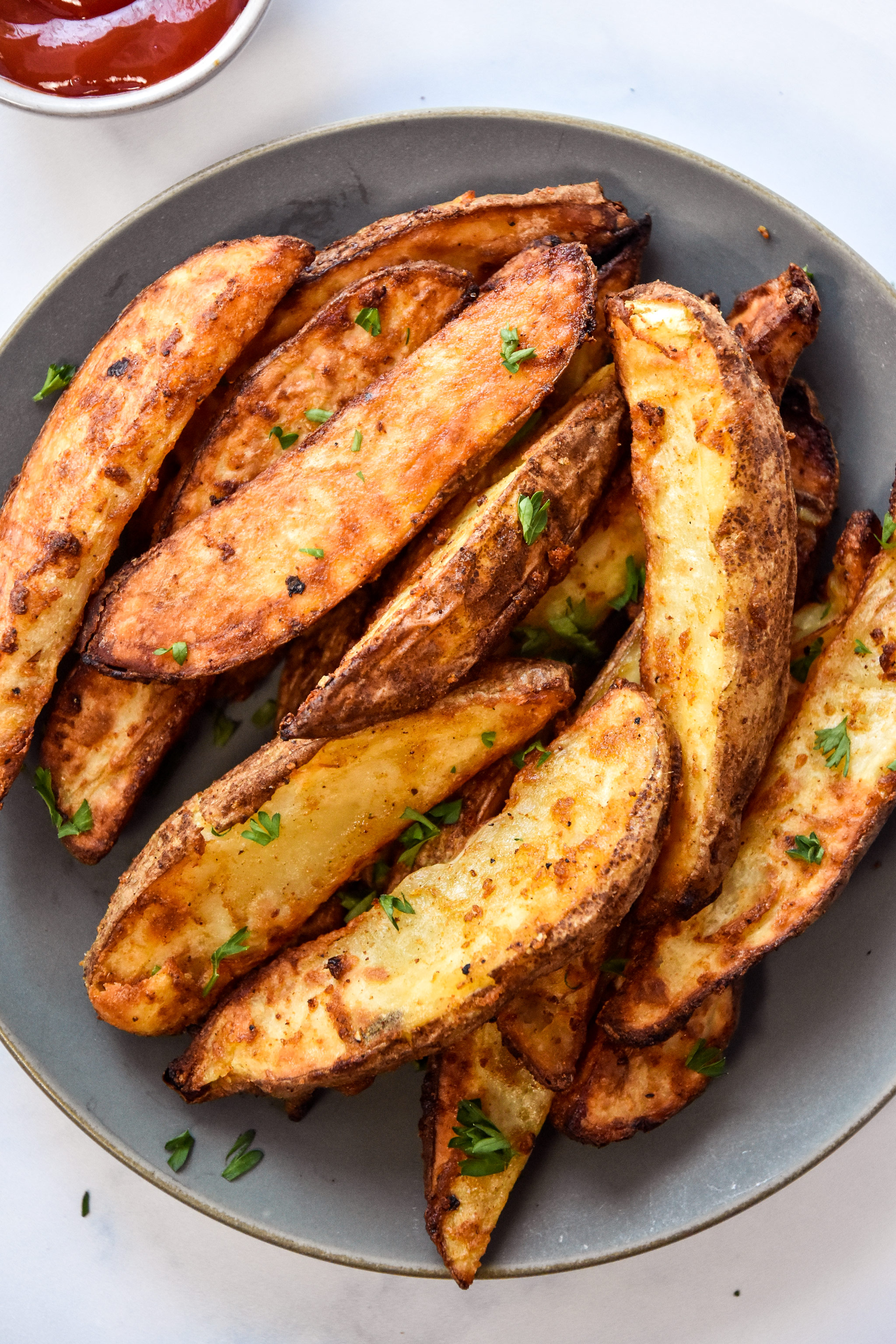 air fryer jojo potatoes wedges on a plate with ketchup on the side.