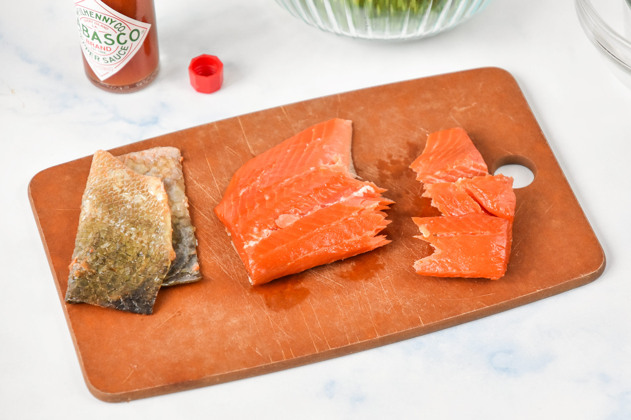 smoked salmon out of the package on a cutting board with the skin removed.