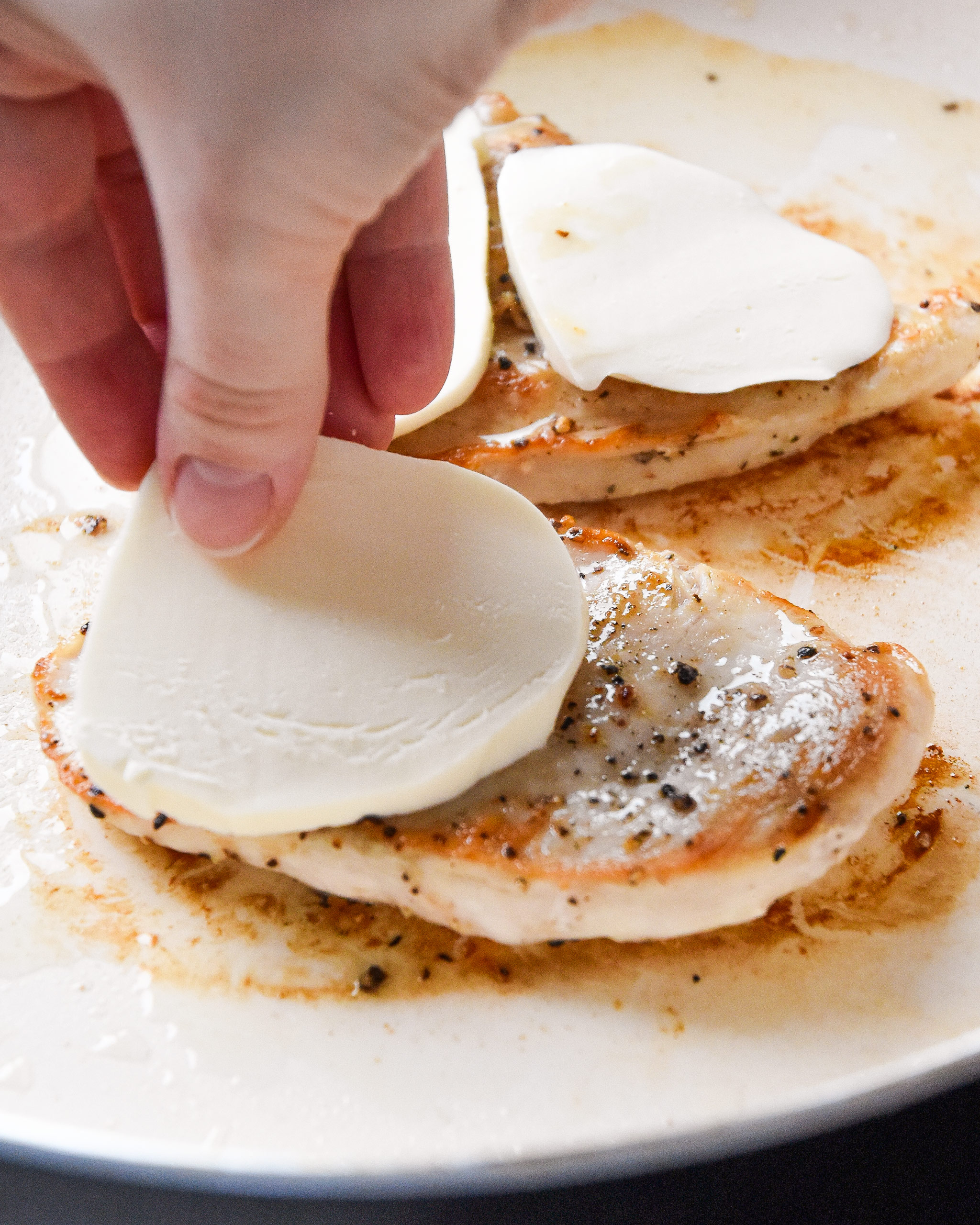 putting mozzarella cheese on the cooking chicken breast.