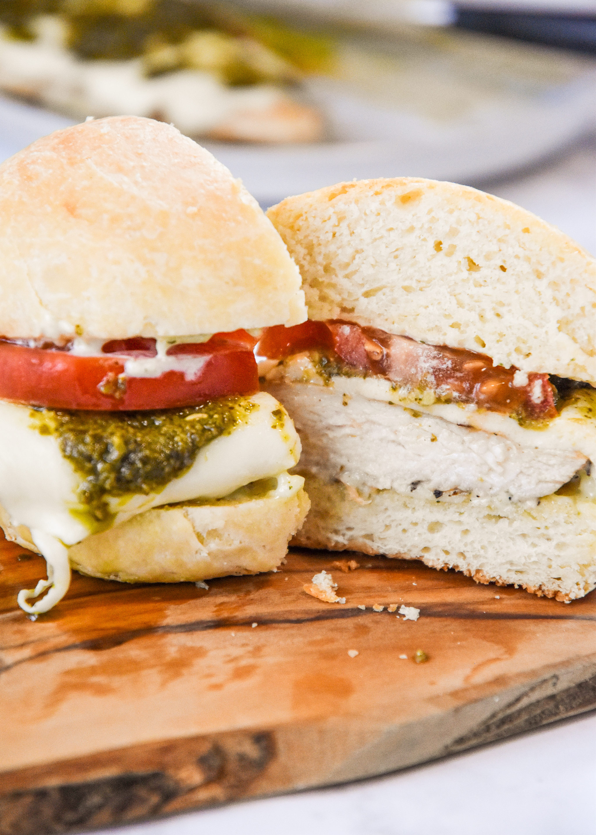 pesto chicken mozzarella sandwich cut in half.