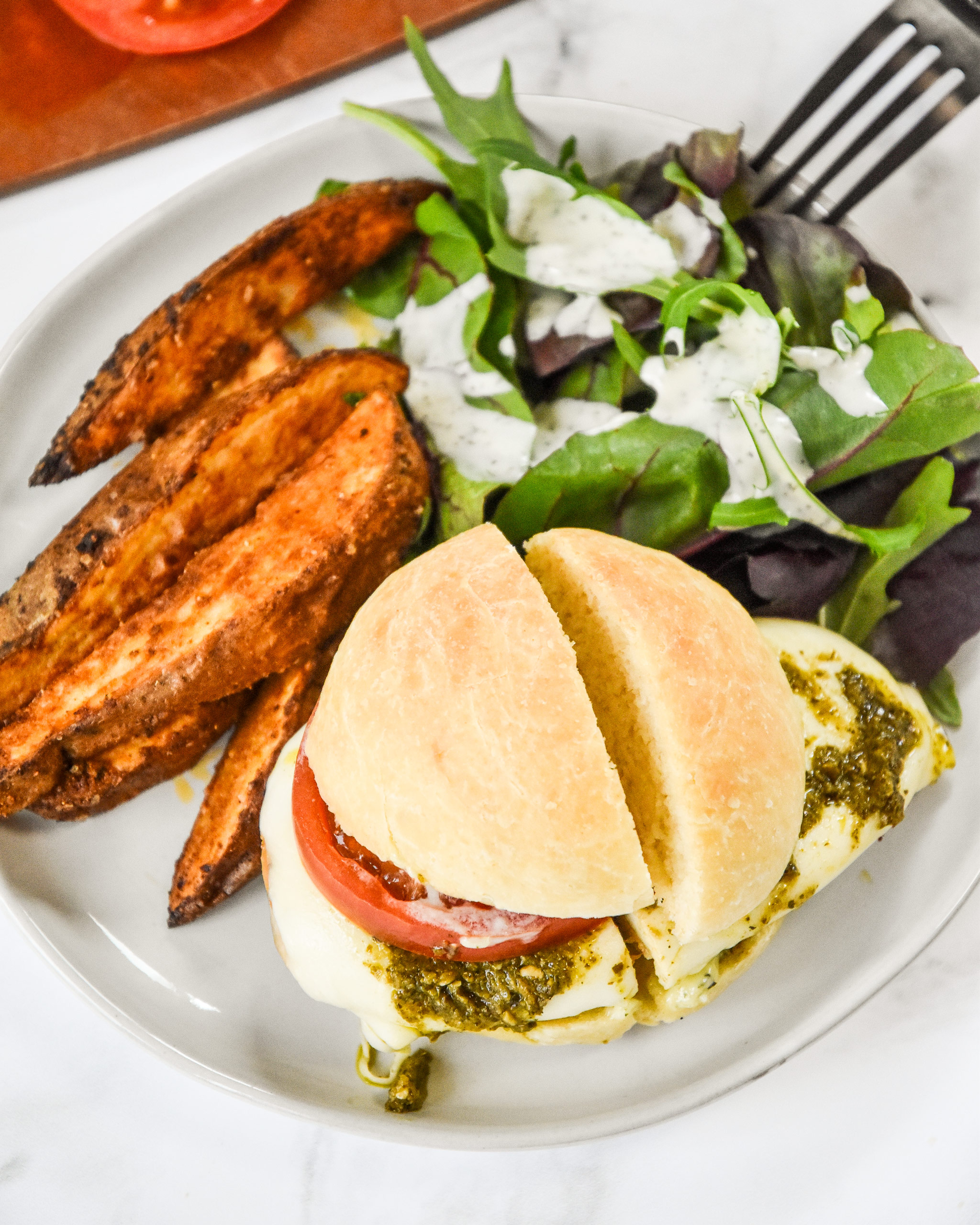 pesto chicken mozzarella sandwich on a plate with potato wedges and a salad.