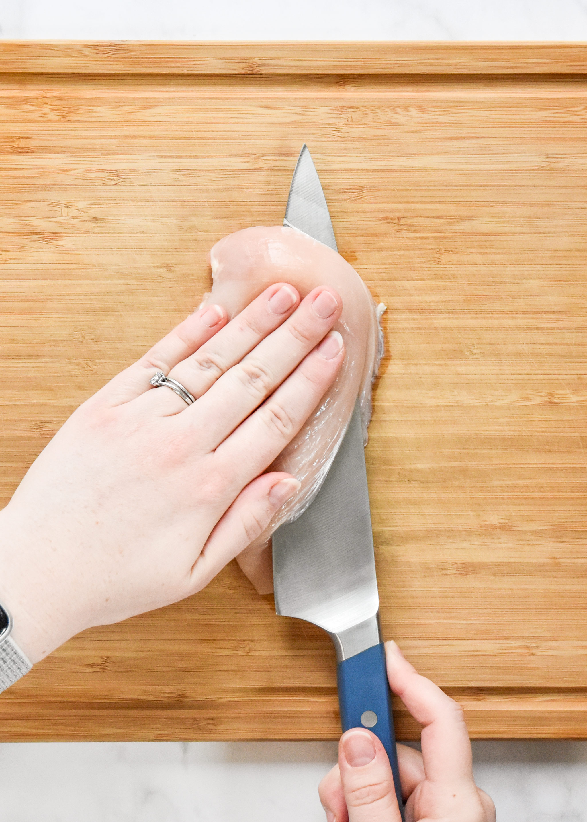 cutting chicken breast in half with a chefs knife.