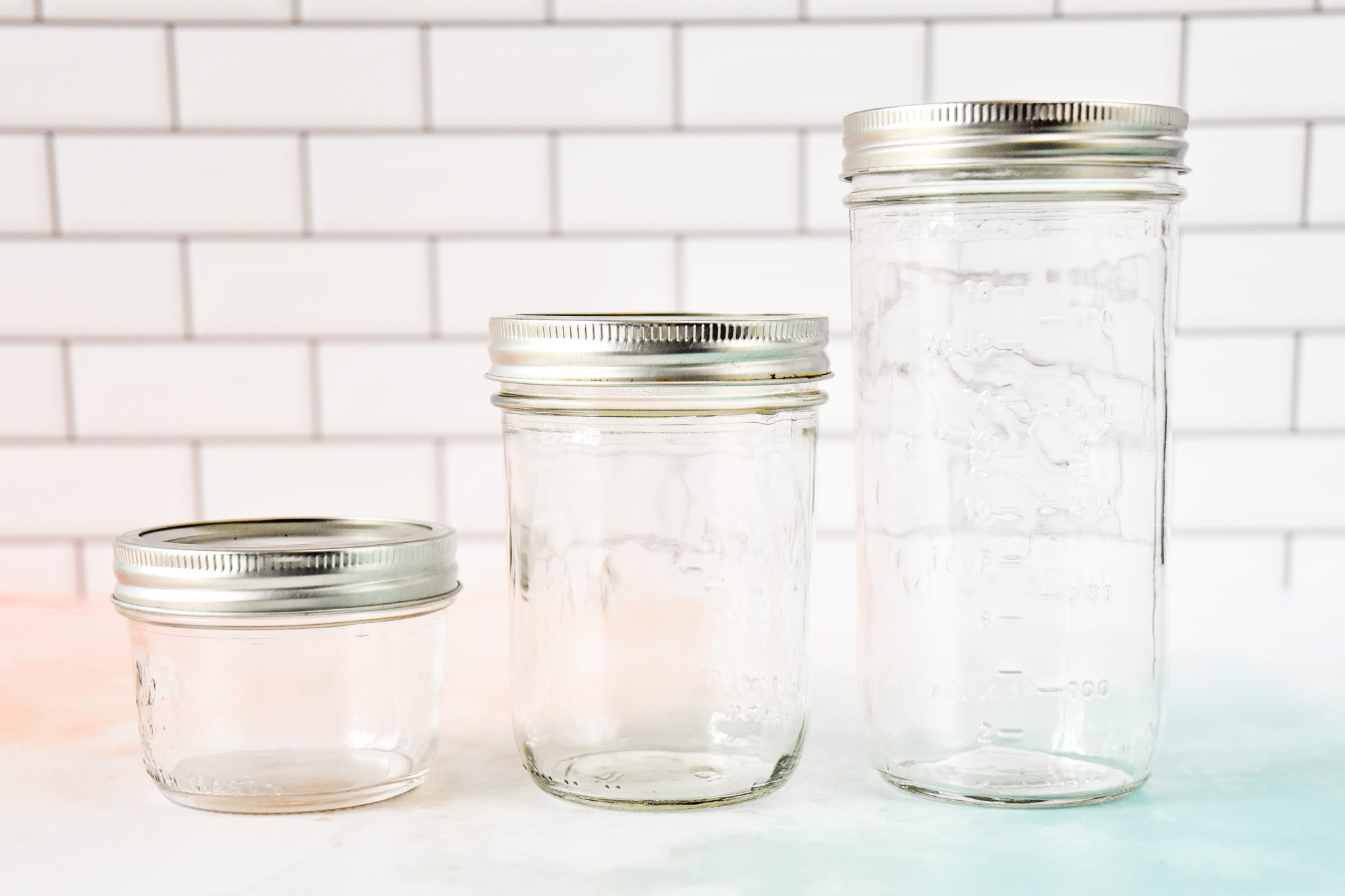 wide mouth mason jars in three sizes on a counter.