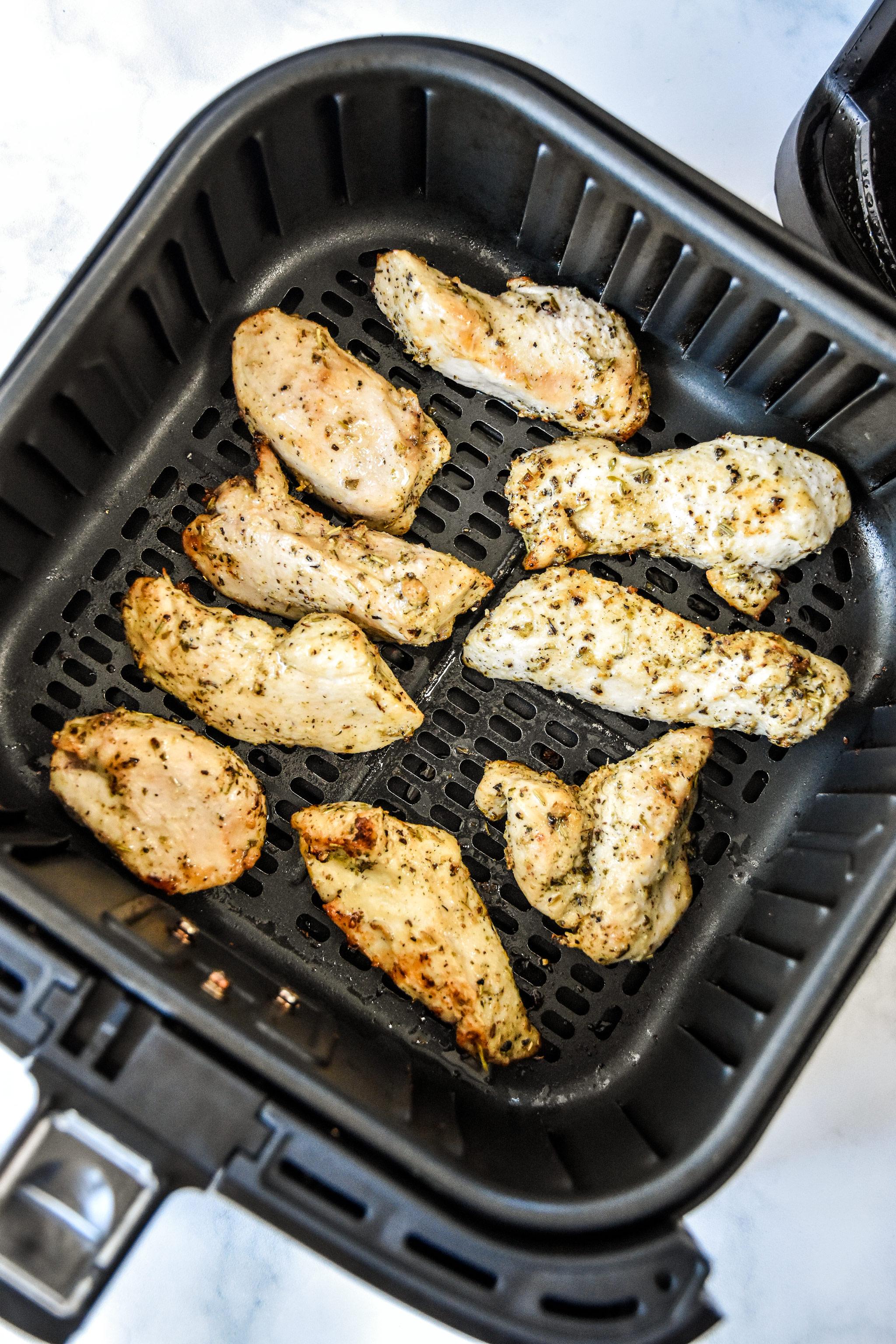 cooked air fryer chicken tenders in the air fryer basket.