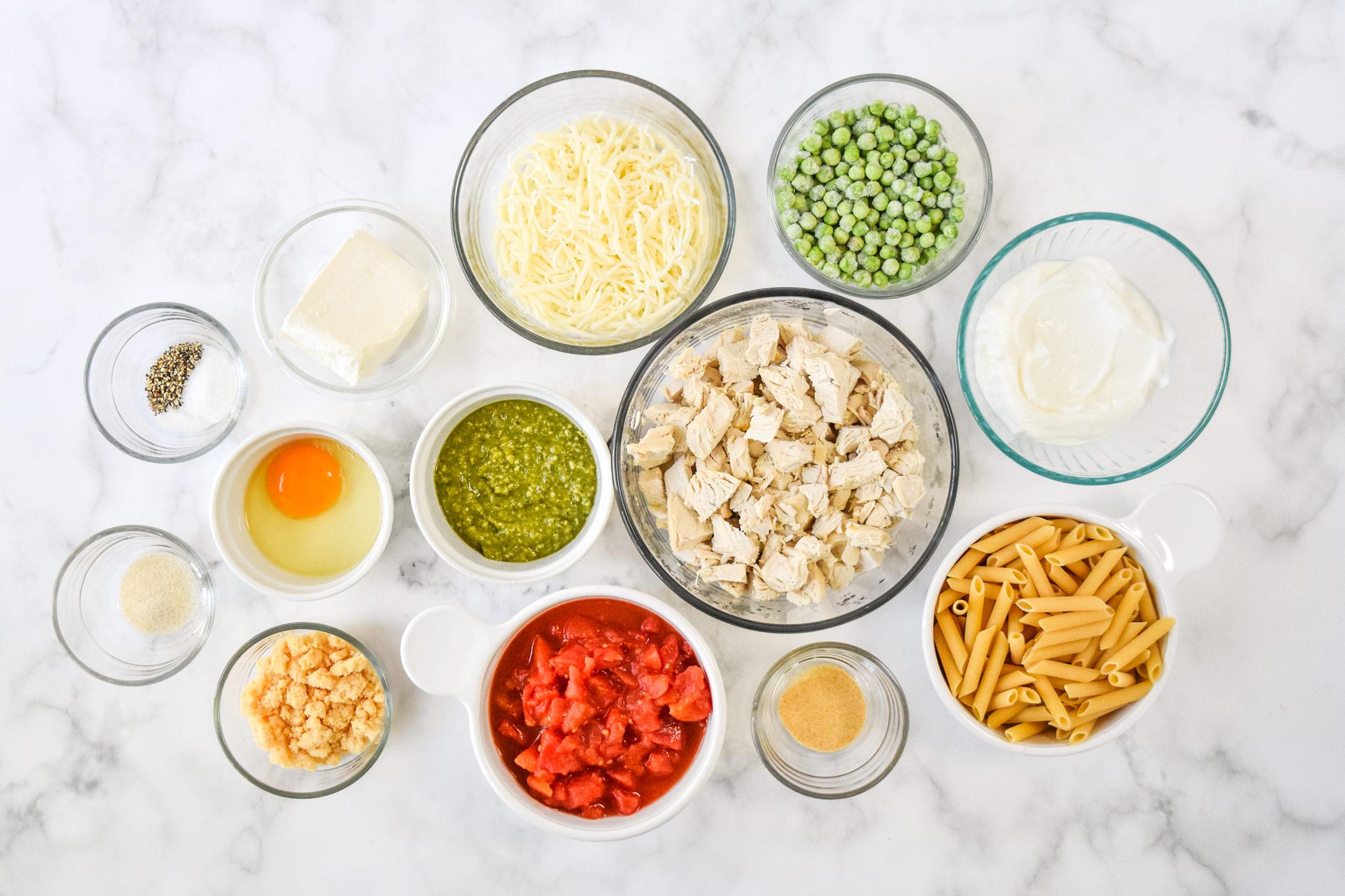 ingredients in bowls ready to make the creamy pesto pasta chicken bake.