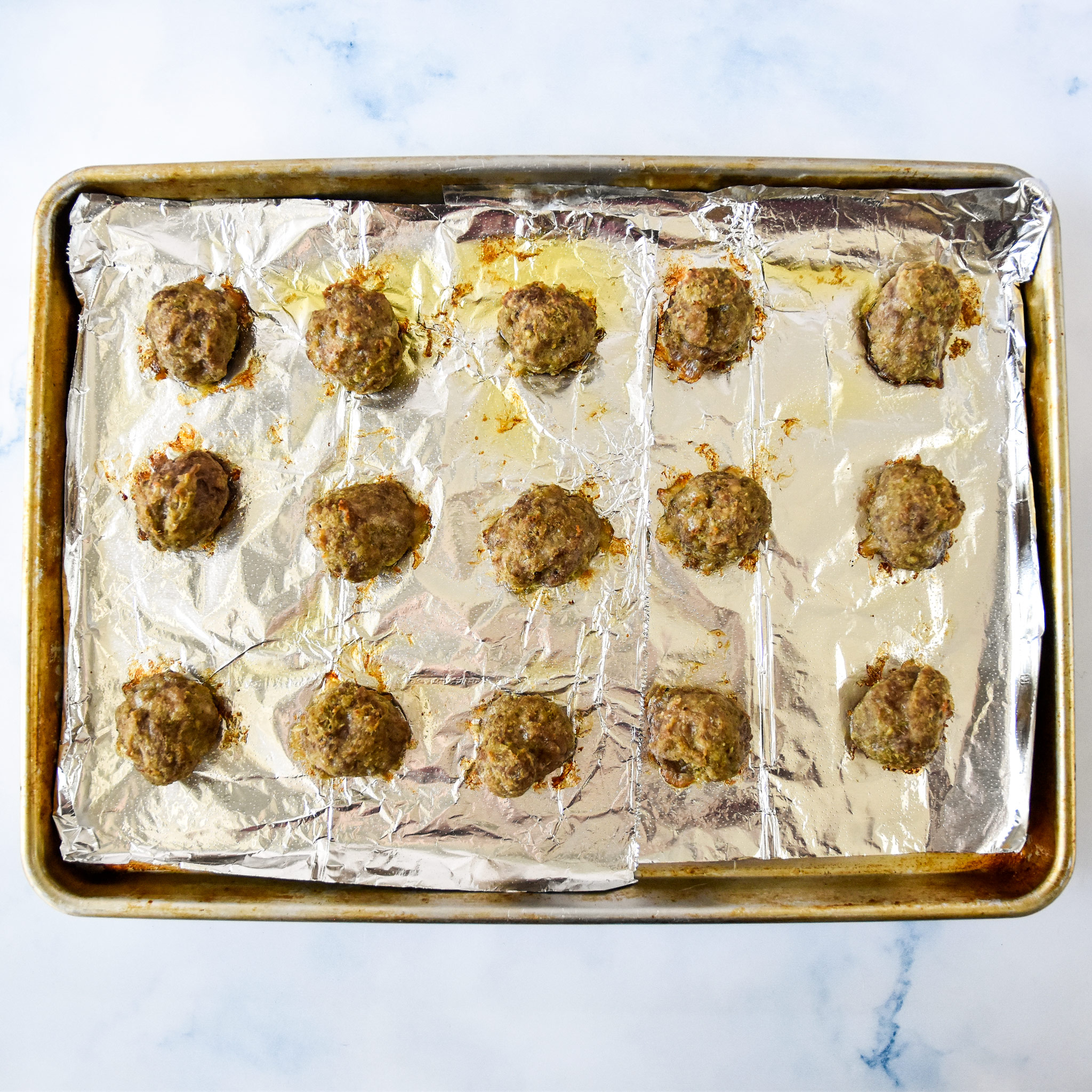 fresh baked easy freezer friendly meatballs on a sheet pan.