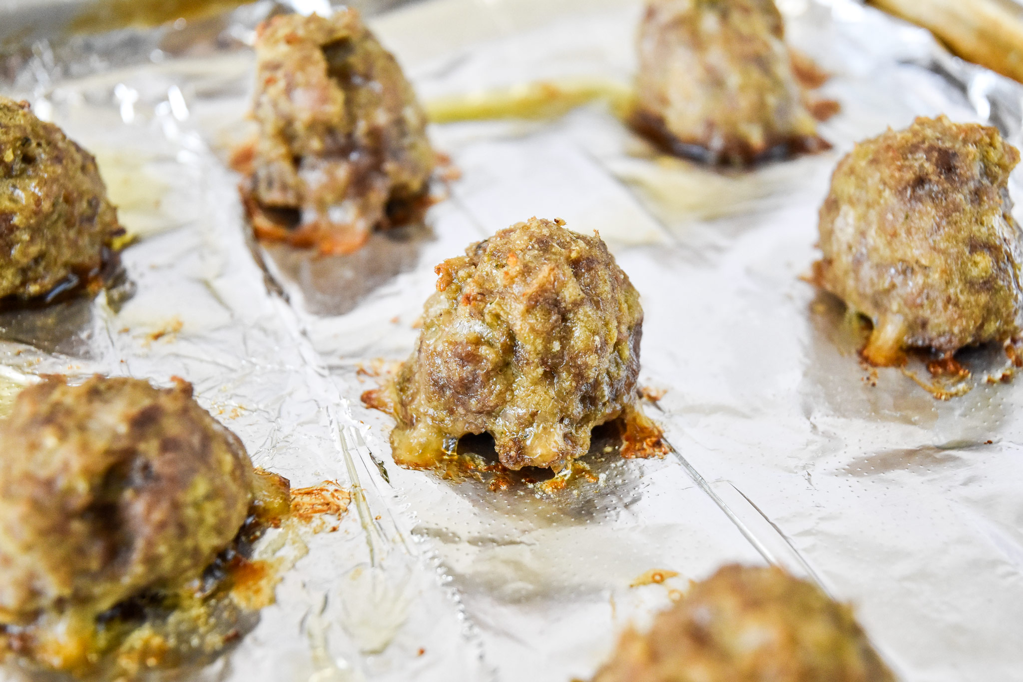 fresh cooked meatballs on a foil lined baking sheet.