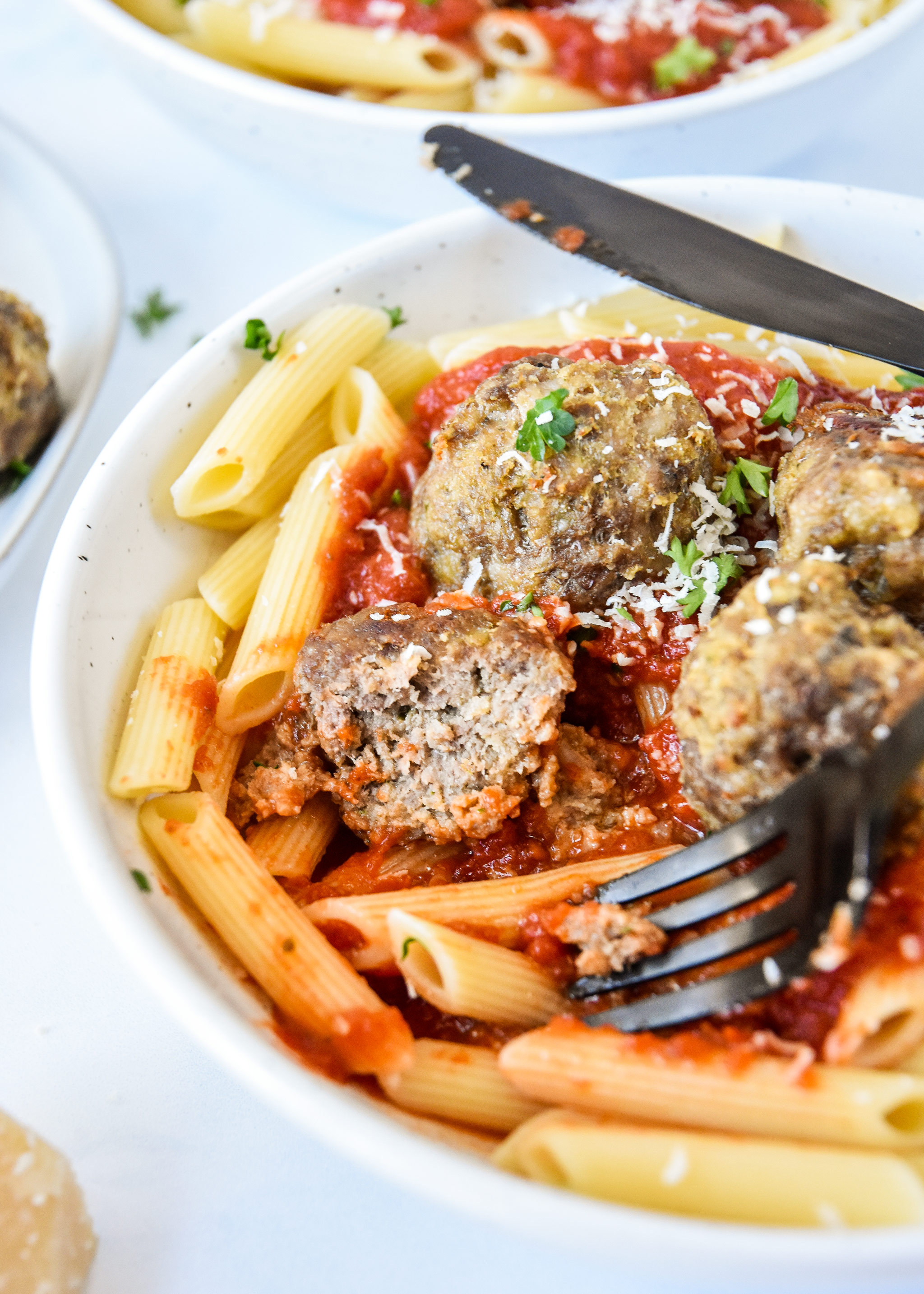 meatball cut in half with pasta and red sauce.