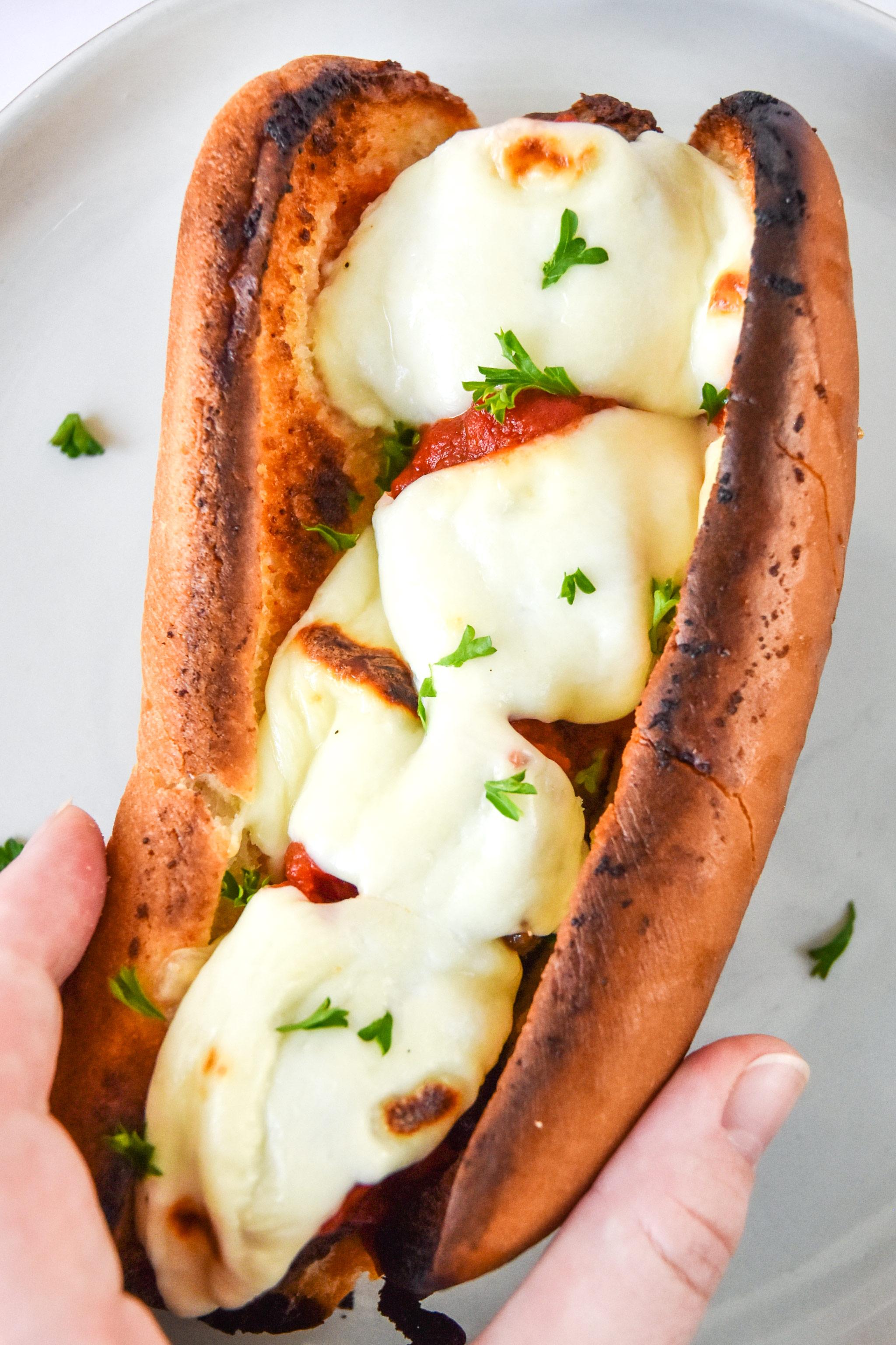 meatball sub sandwich with fresh mozzarella in hand.