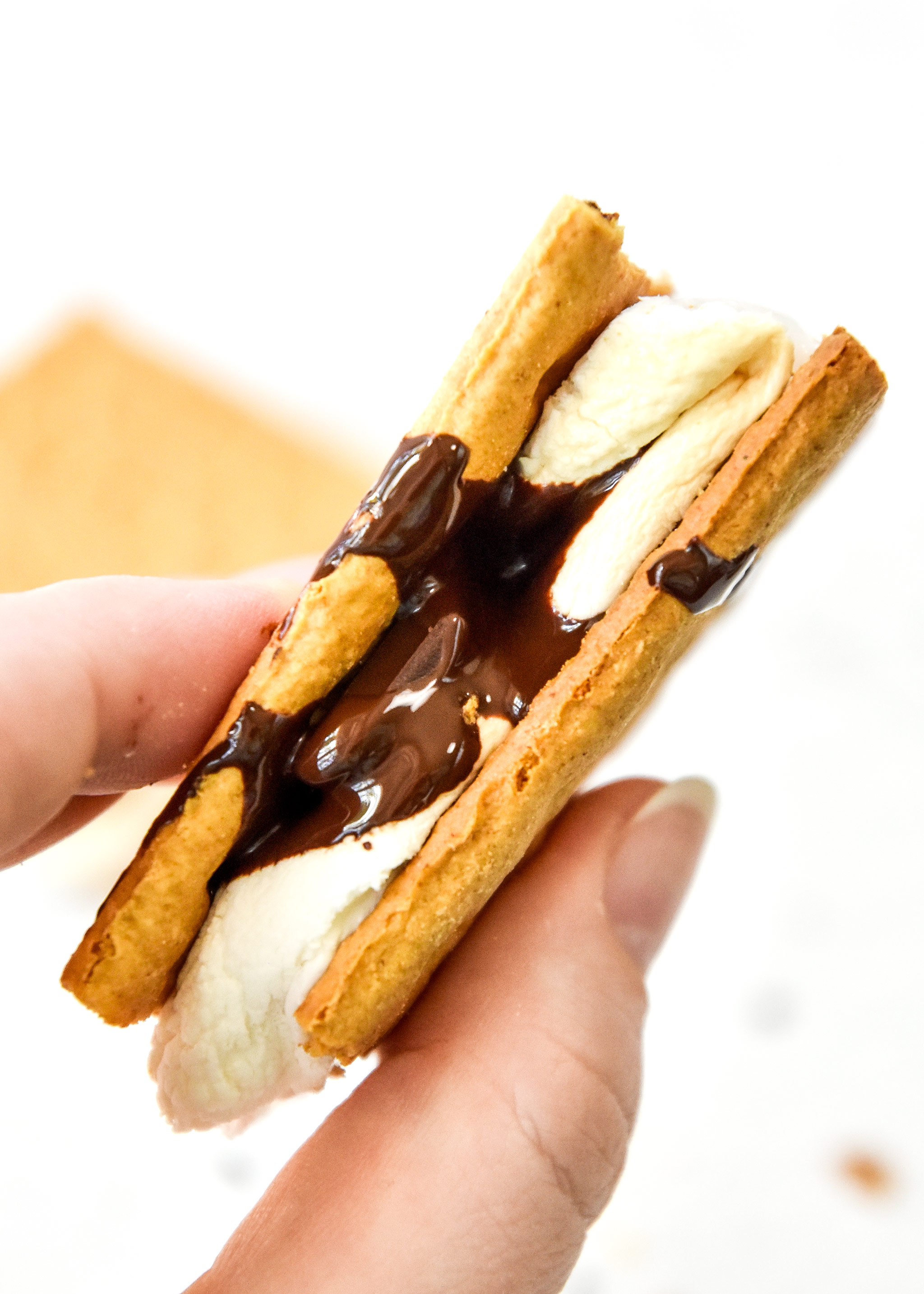 freshly made air fryer s'more with dripping chocolate in hand.