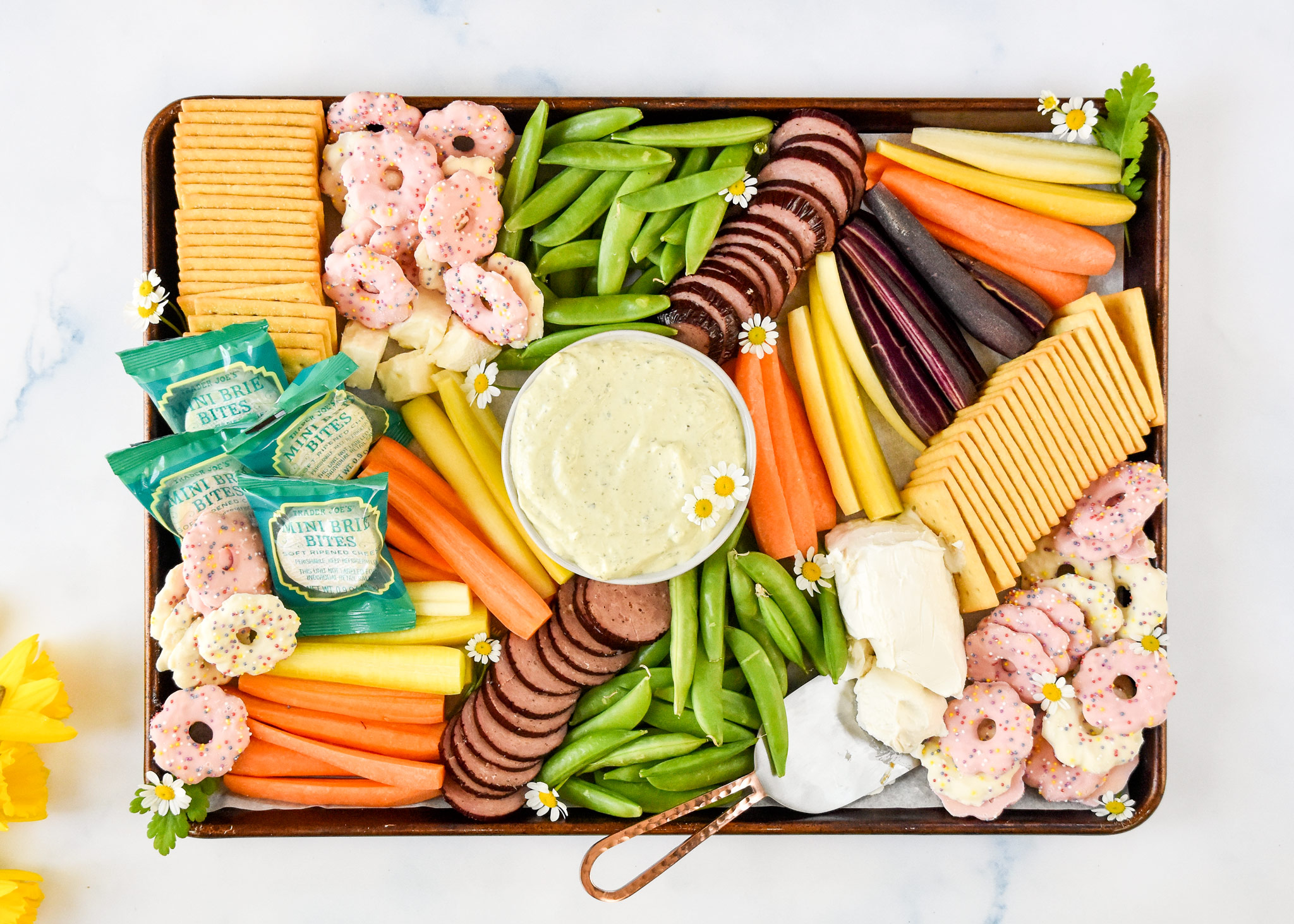 easy trader joes spring snack board finished with flowers and tons of veggies, crackers and cheese.