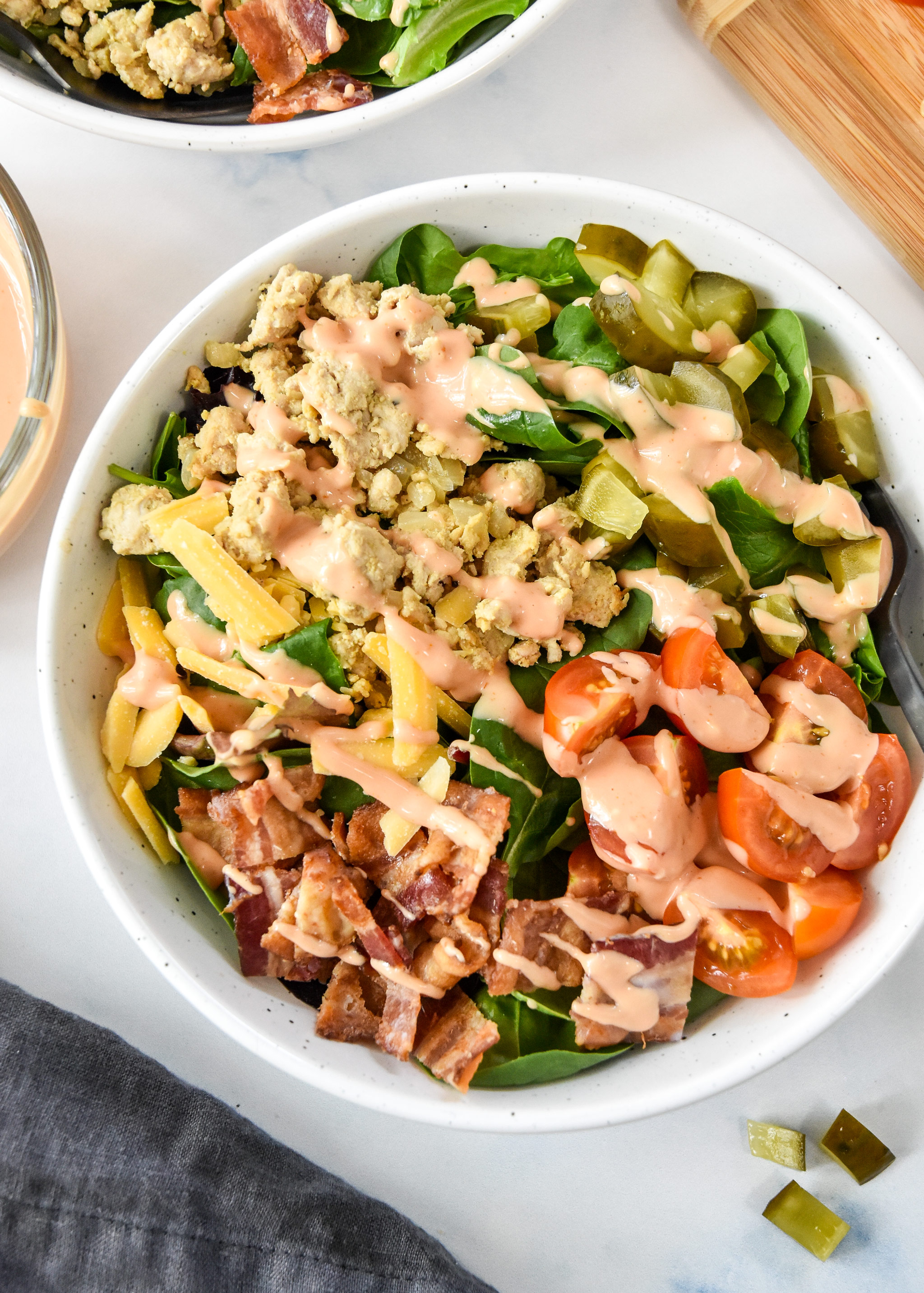 ground turkey burger salad with bacon cheese pickles, serve in a white bowl with special sauce dressing.