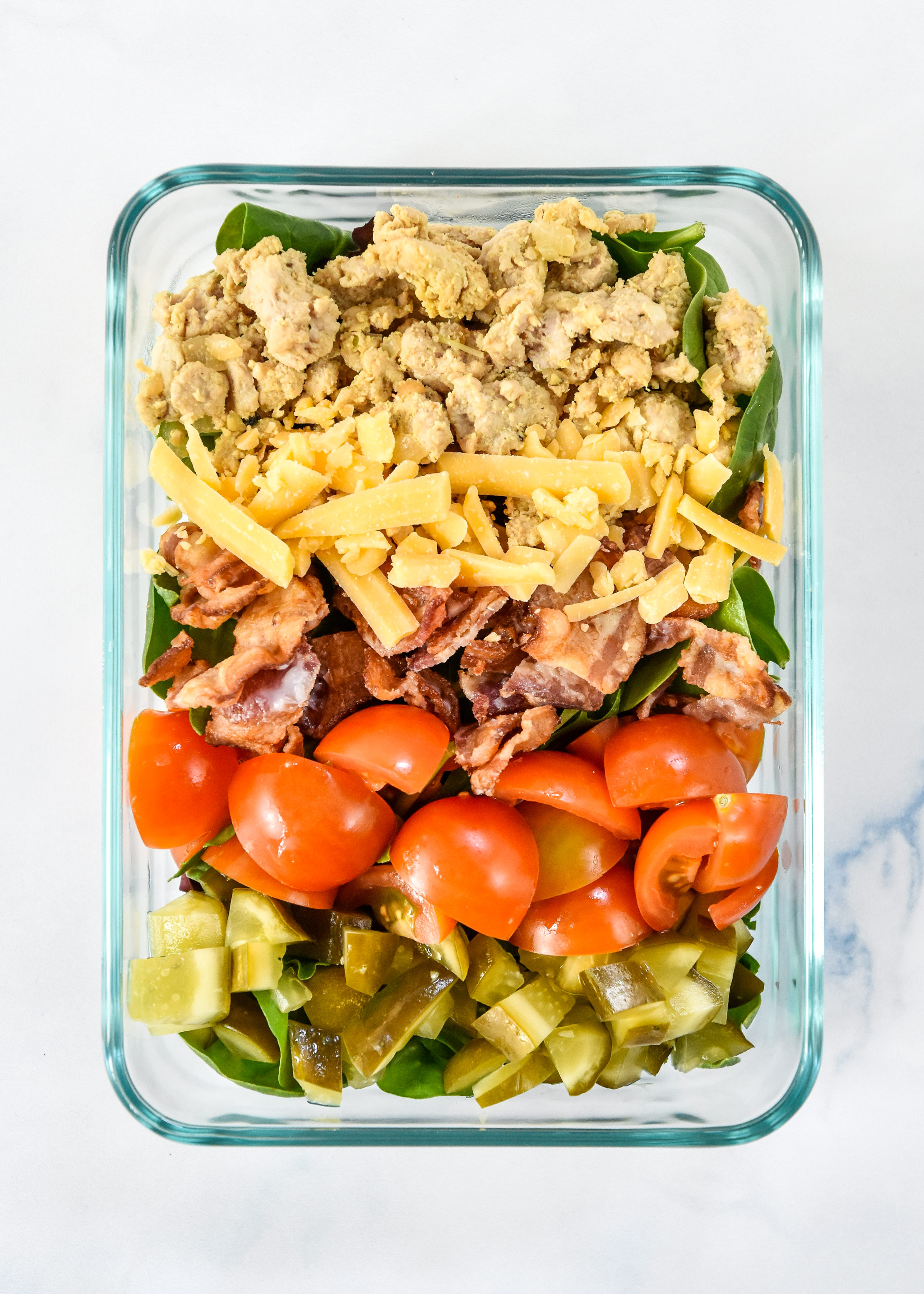 loaded ground turkey burger salad in a glass meal prep bowl.