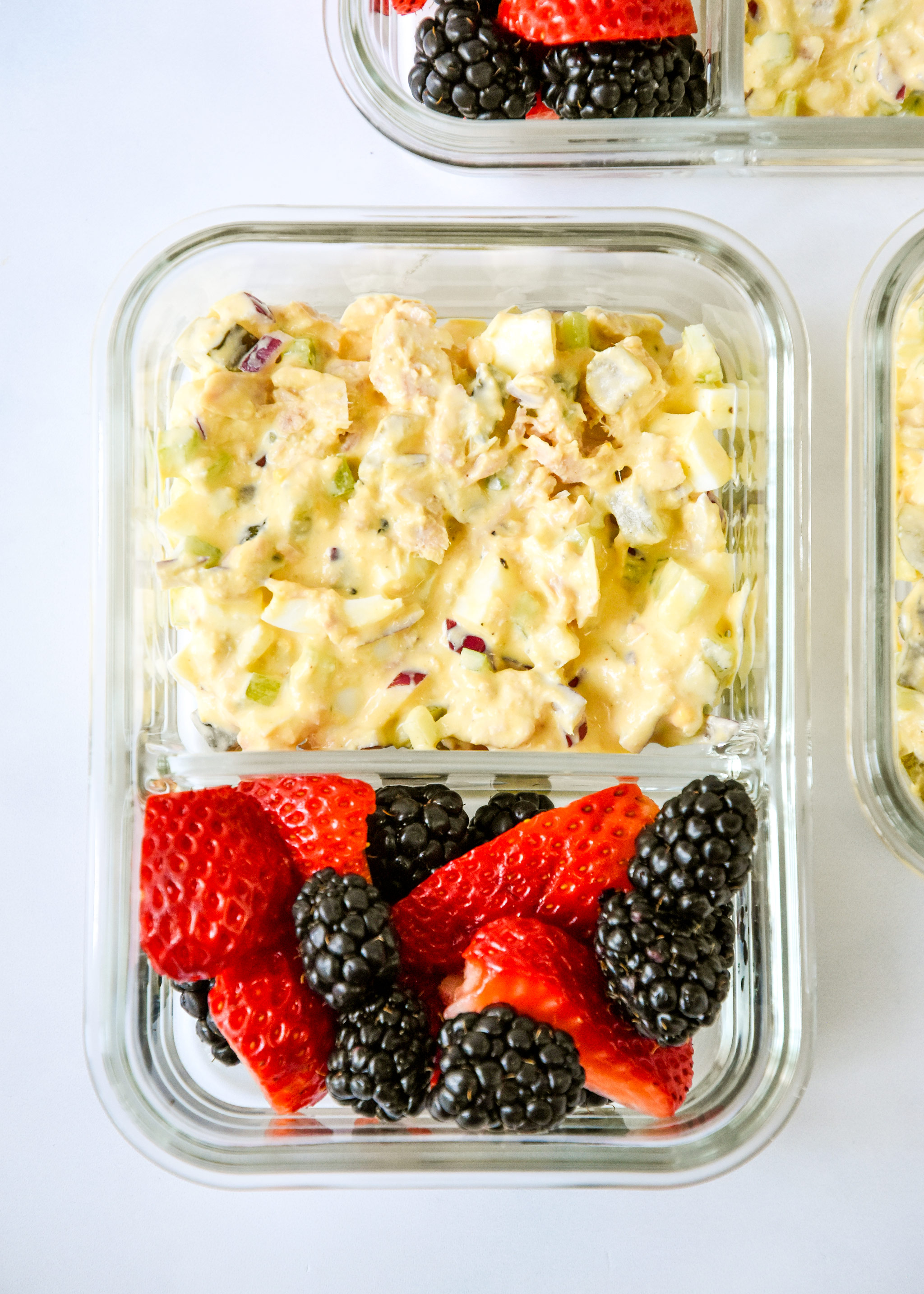 tuna egg salad in a meal prep container with fresh berries.