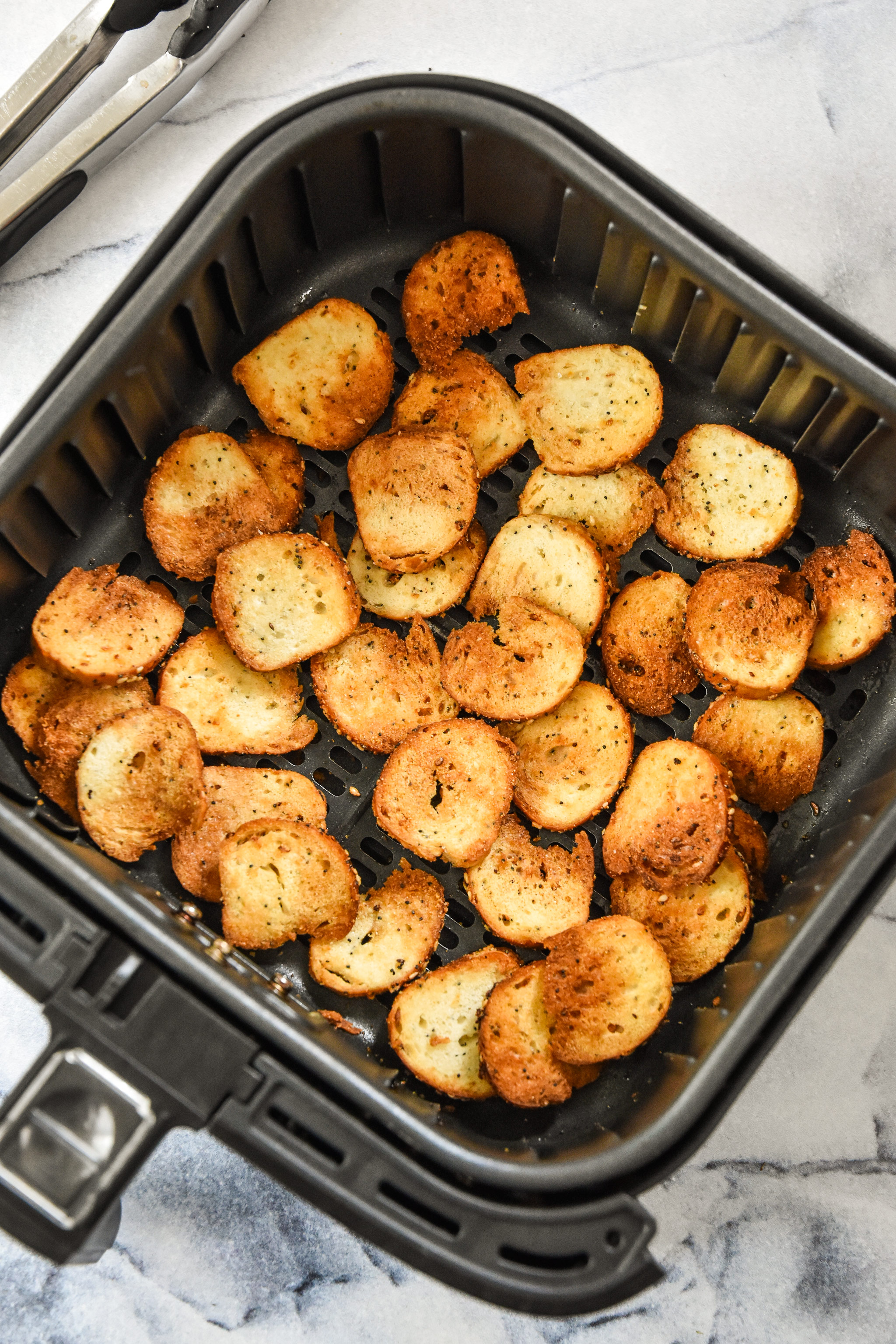 cooked bagel chips in the air fryer basket.