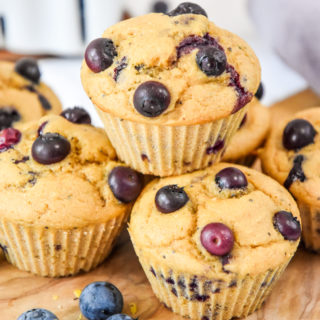 stacked muffins on a cutting board.