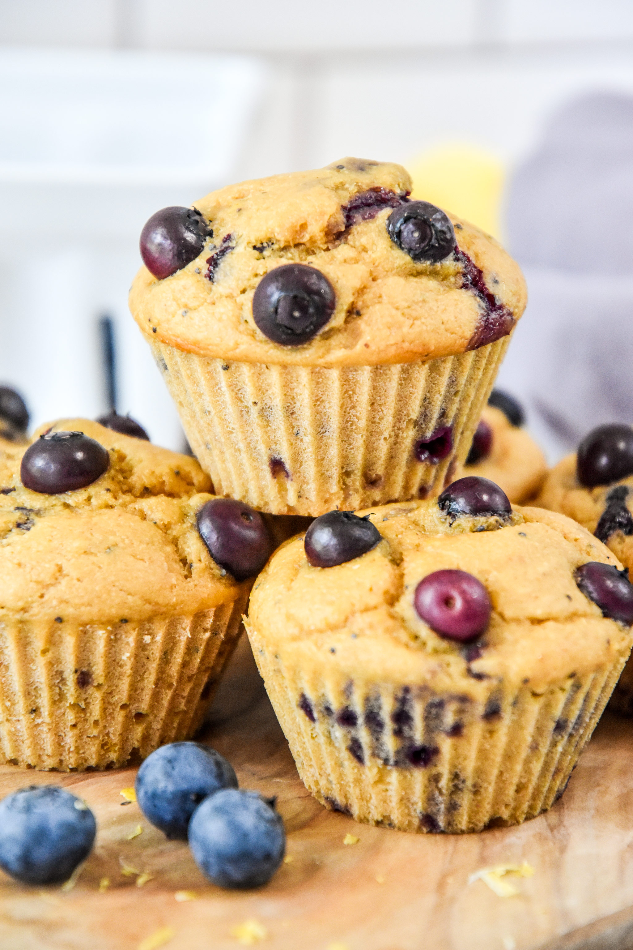 muffins stacked on a cutting board with blueberries.