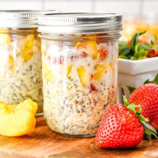 mason jar full of strawberry peach overnight oats on a cutting board.