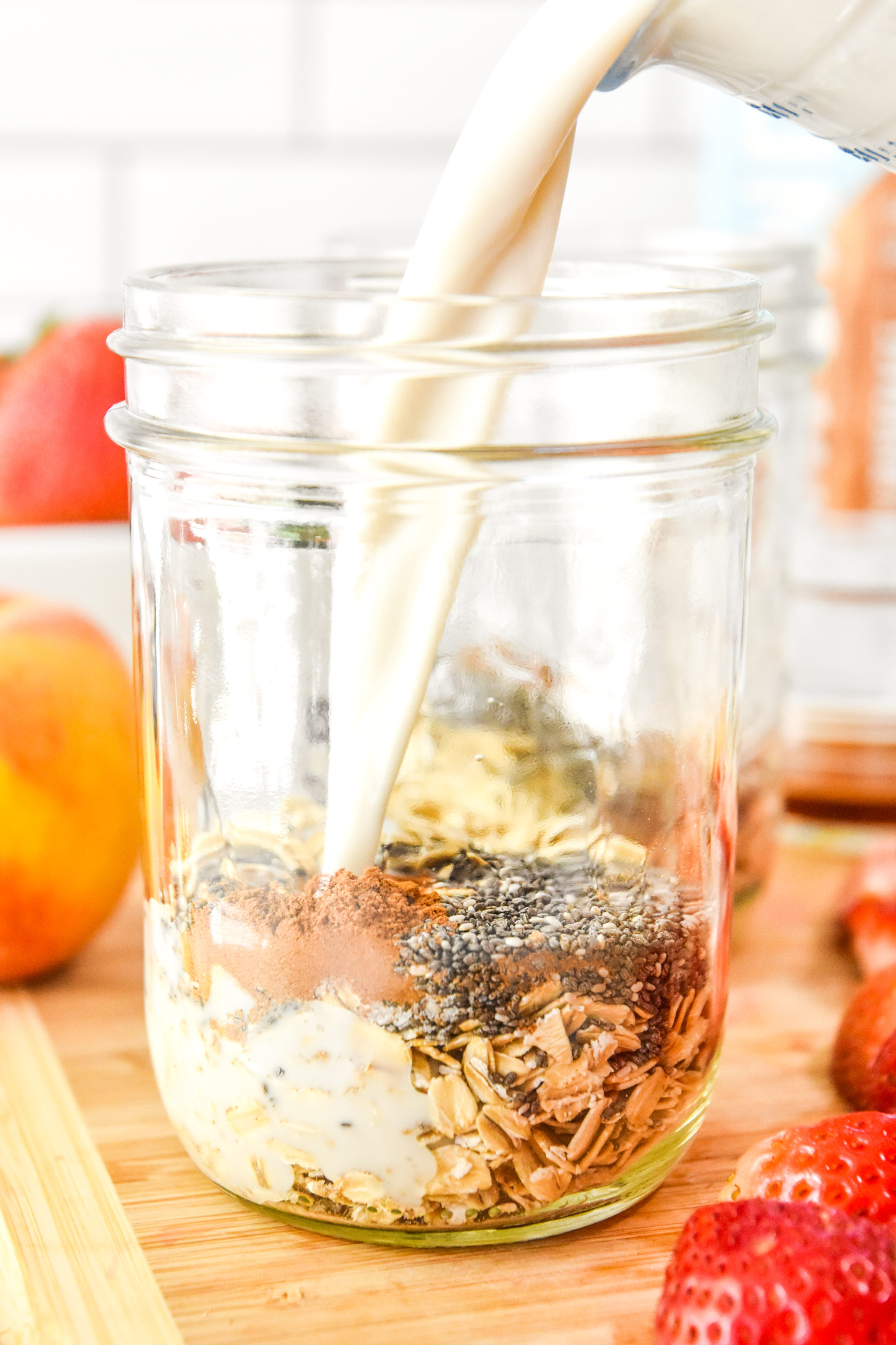 pouring milk into the mason jars for each serving of strawberry peach overnight oats.