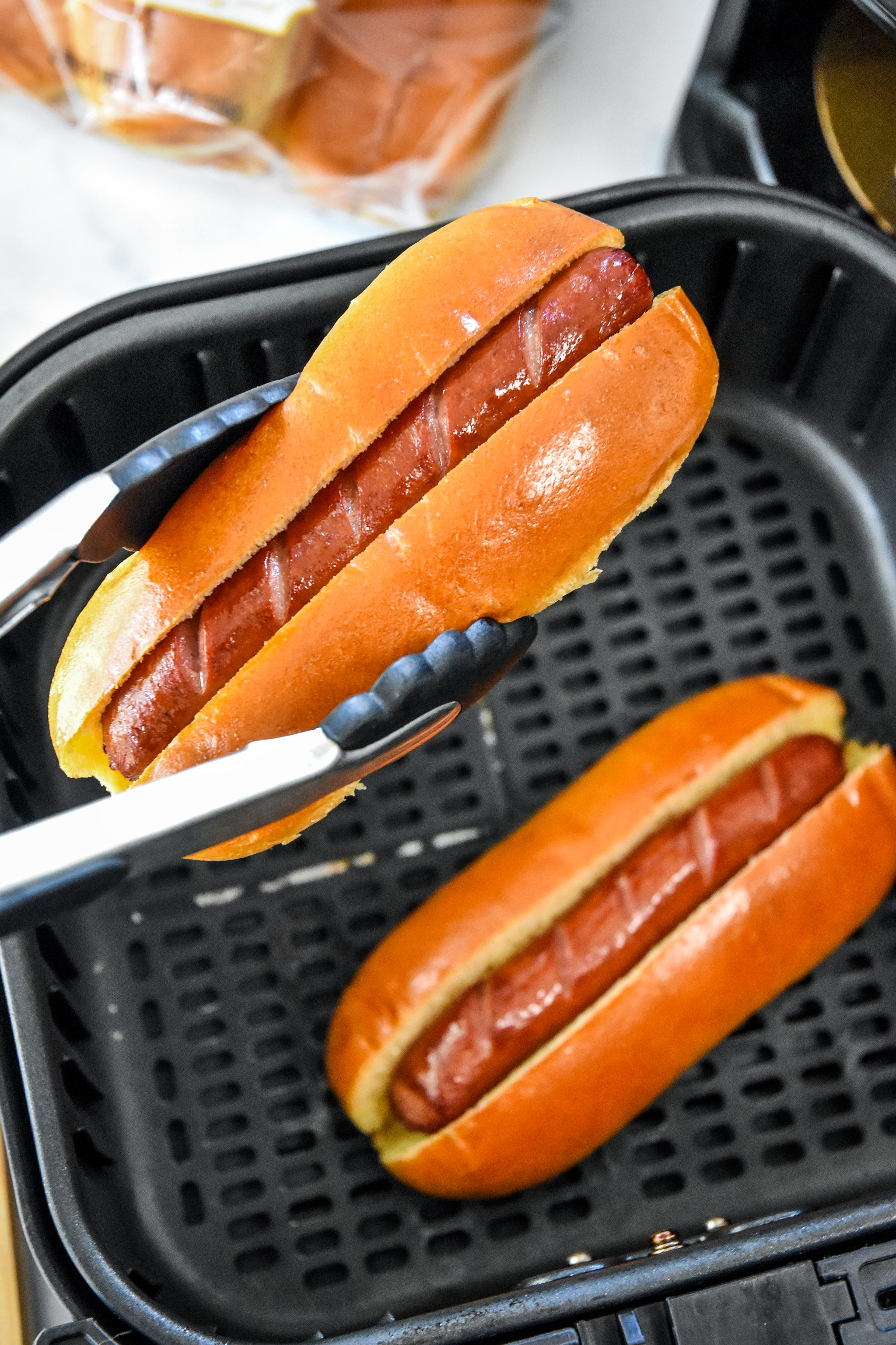 buns and hot dogs going into the air fryer basket.