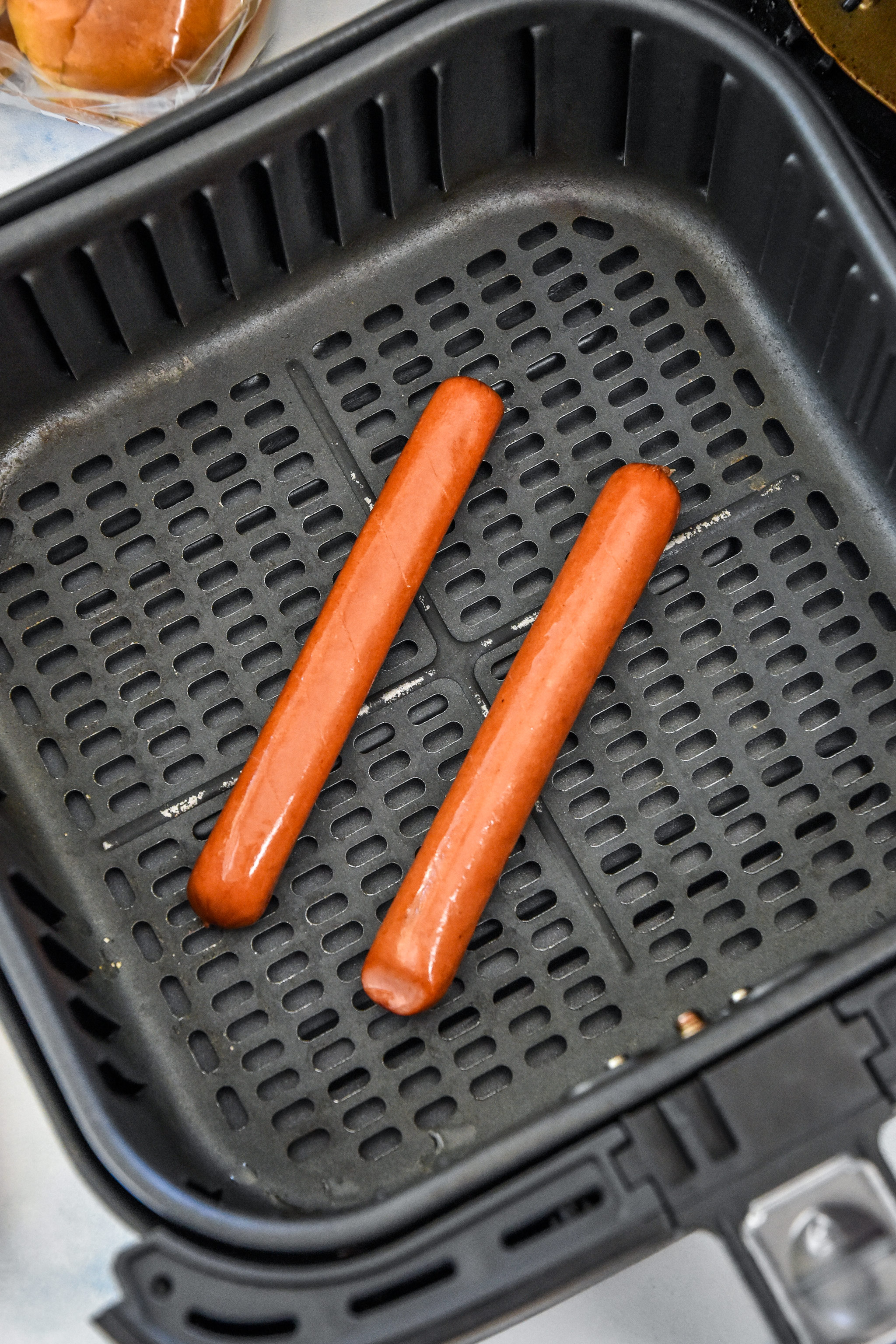 hot dogs in the air fryer basket about to be cooked.