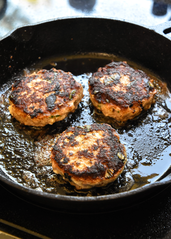 feta basil turkey burgers cooking in a cast iron skillet.