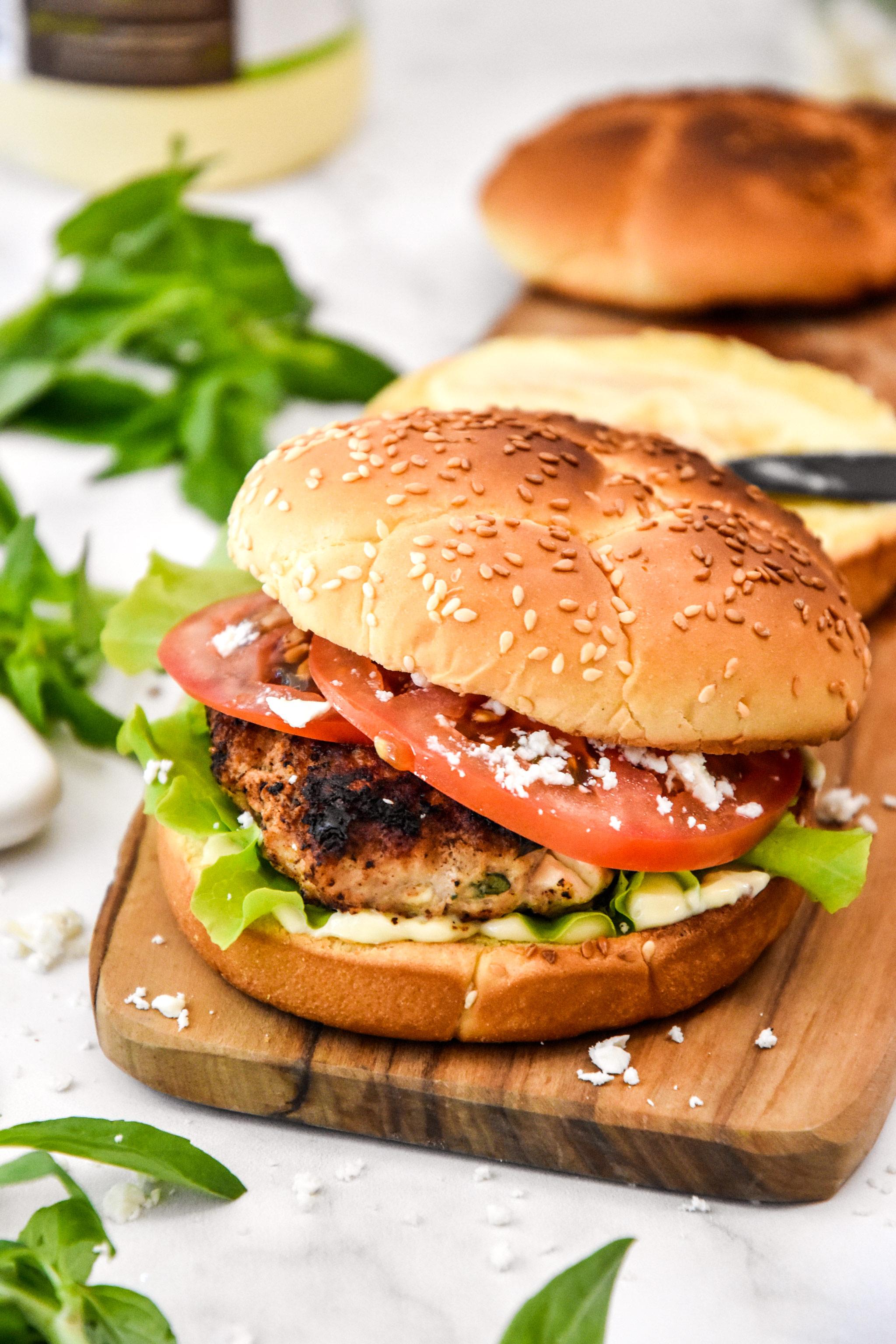 assembled feta basil turkey burger on a cutting board.