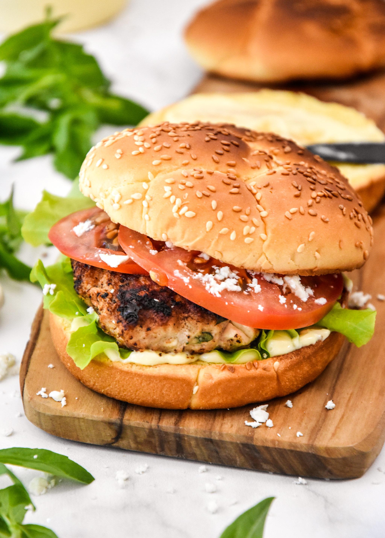 Feta Basil Turkey Burger on a bun with tomato and lettuce.