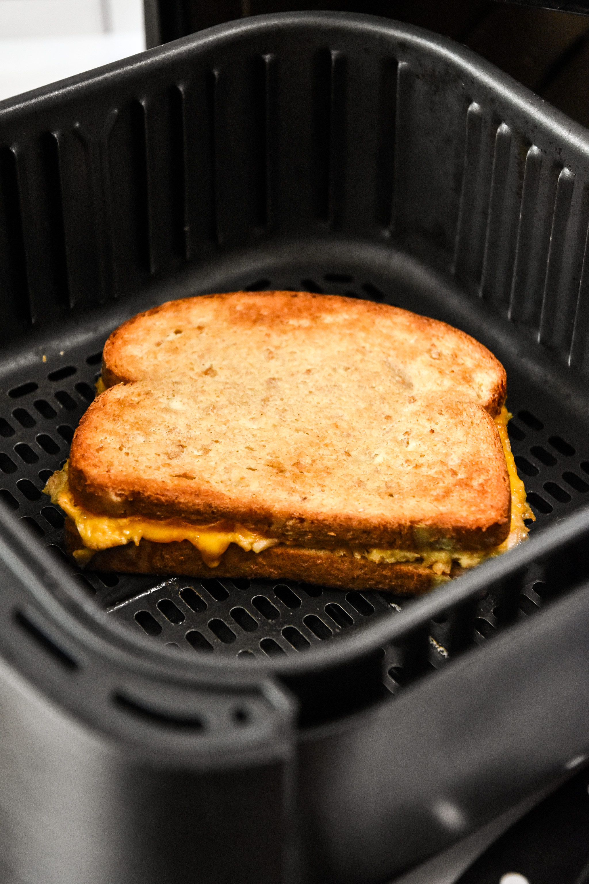 cooked air fryer tuna melt in the air fryer basket.