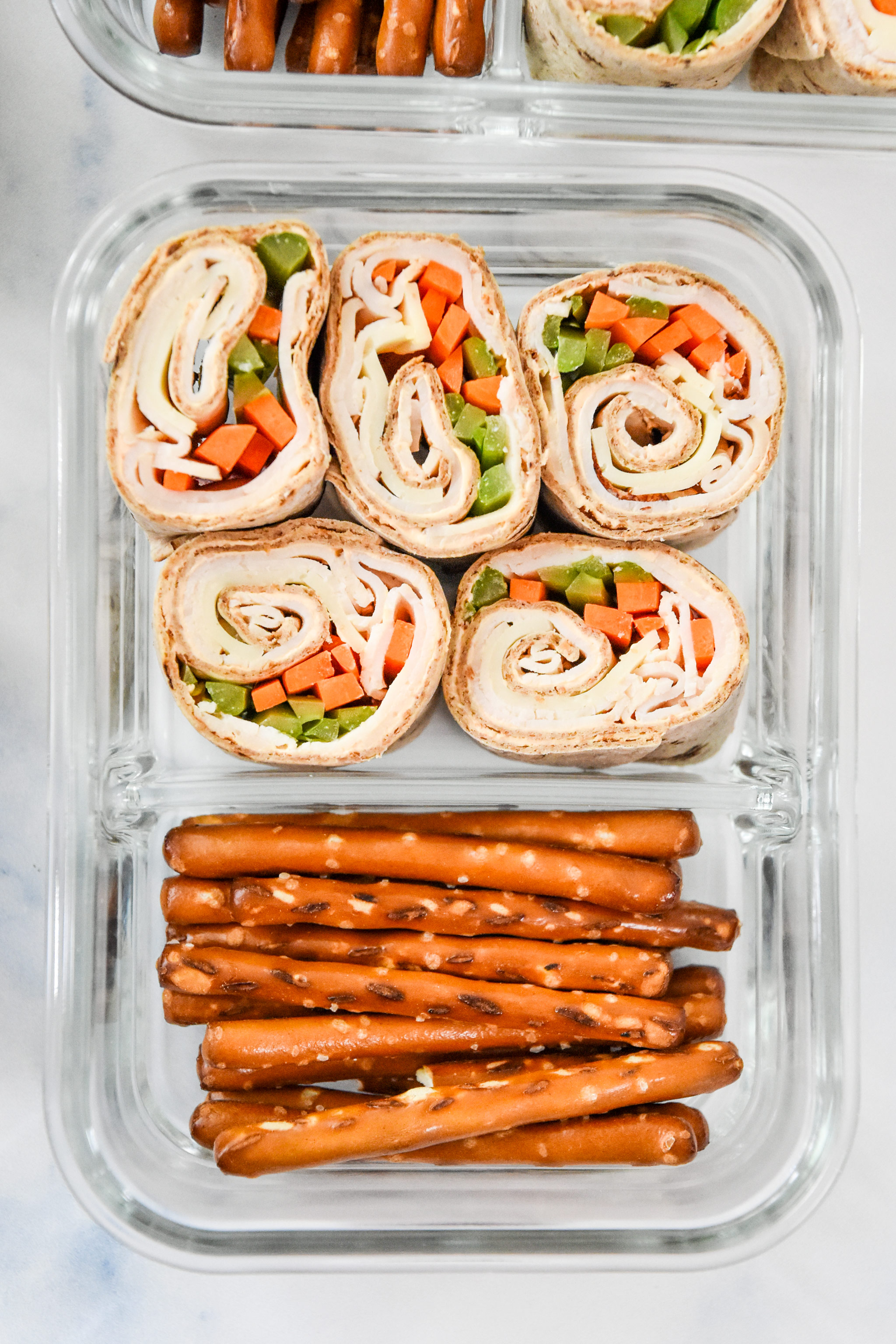 buffalo chicken pinwheels meal prep with pretzels in a glass container.