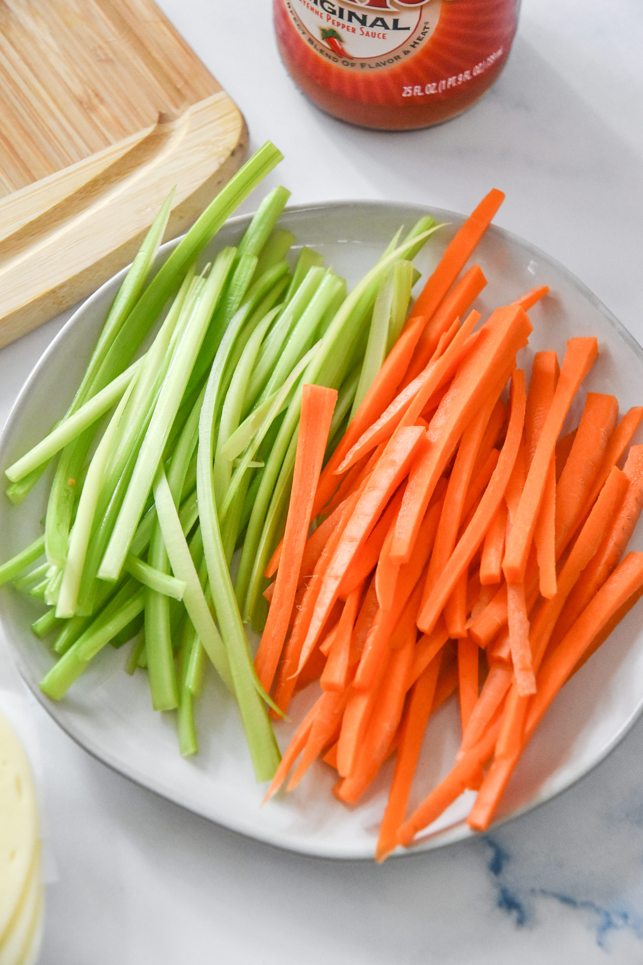 julienned carrots and celery on a plate.
