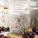 cherry vanilla overnight oats in a mason jar with a gold spoon.