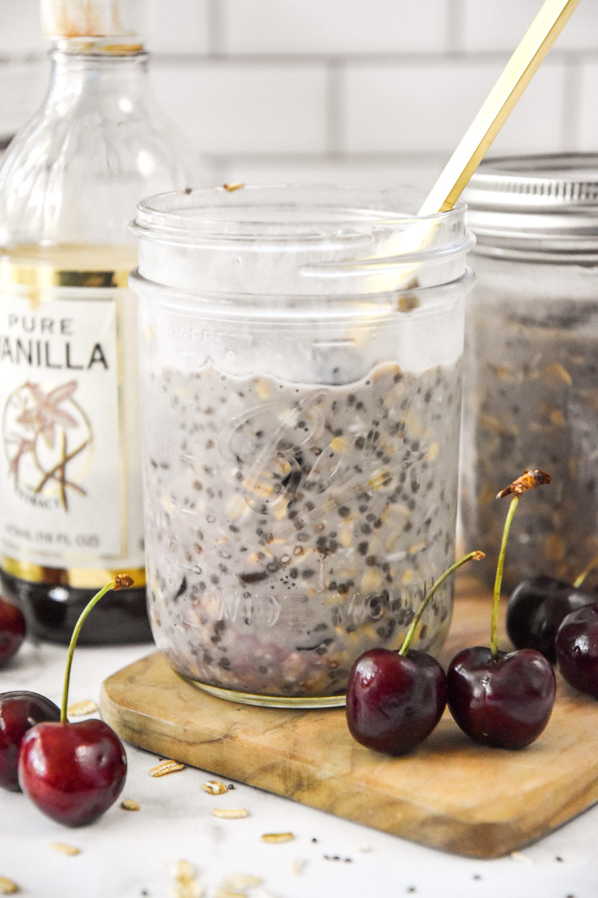 cherry vanilla overnight oats in a mason jar with cherries around.