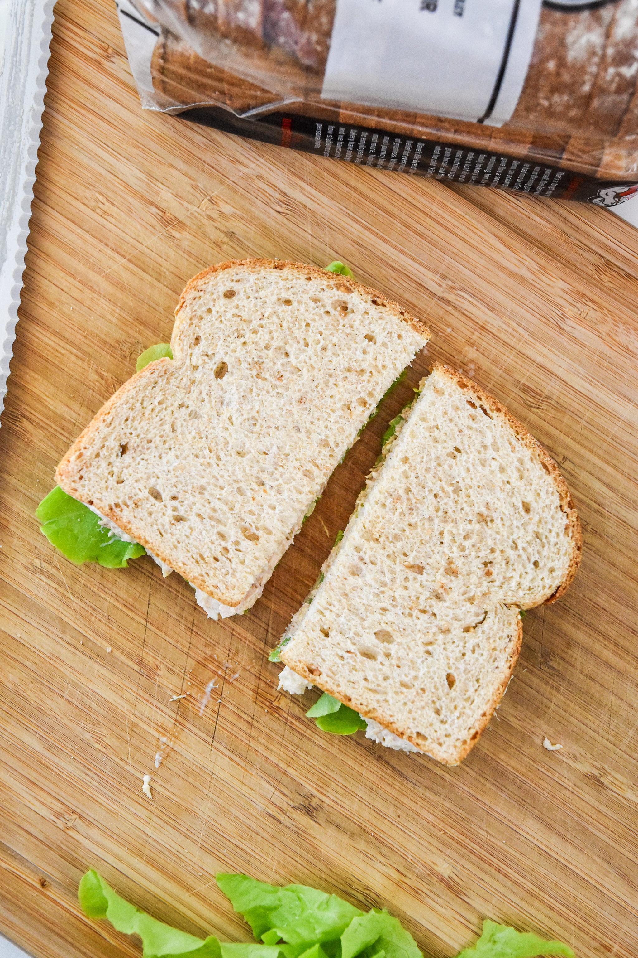tuna sandwich made with lazy no chop tuna salad cut in half on a cutting board.