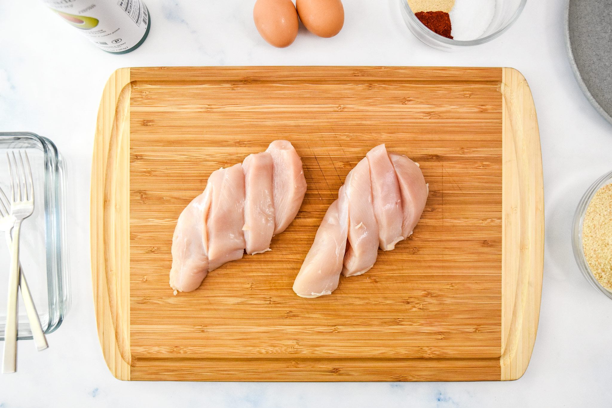 chicken breasts sliced on a cutting board to make chicken tenders.